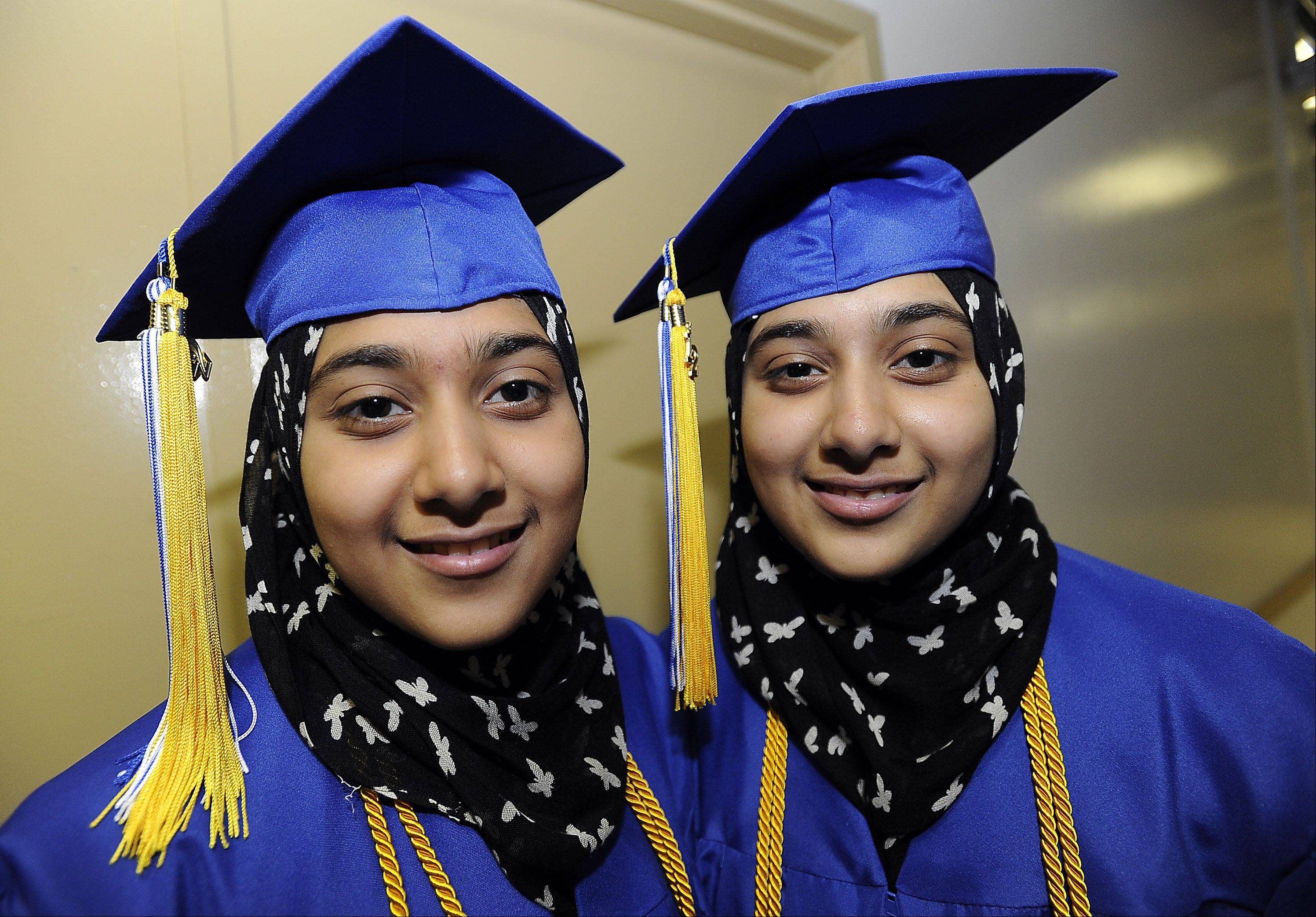 Twins Shamail and her Mashail Siddiqui ,18, of Des Plaines prepare to graduate with high honors at the Akoo Theatre in Rosemont on Monday during Maine East's commencement.