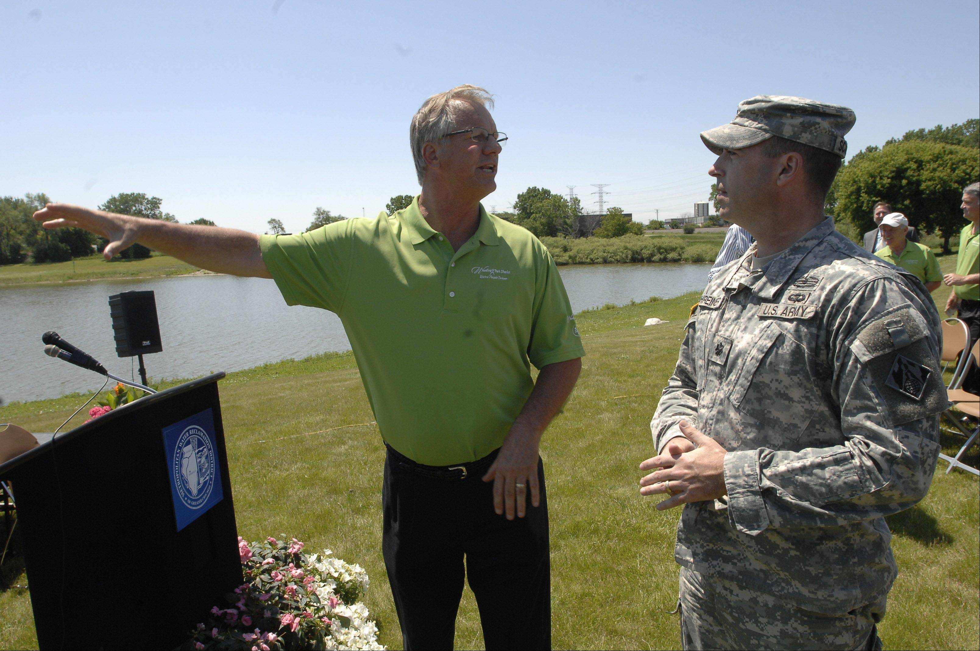Wheeling park board President Keith Pecka, left, talks with Lt. Col. James Schreiner of the Army Corps of Engineers as ground was broken Monday for the Heritage Park Flood Control Facility in Wheeling.