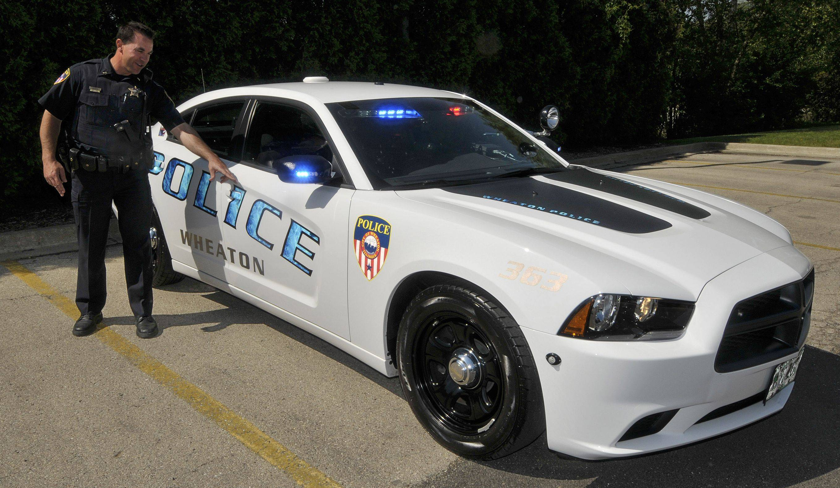 Wheaton police officers show off their new squad car, a Dodge Charger. It has features not possible on their old Ford Crown Victorias, and the new paint scheme follows the curves of the car body, as pointed out by Lt. Robert Miller.