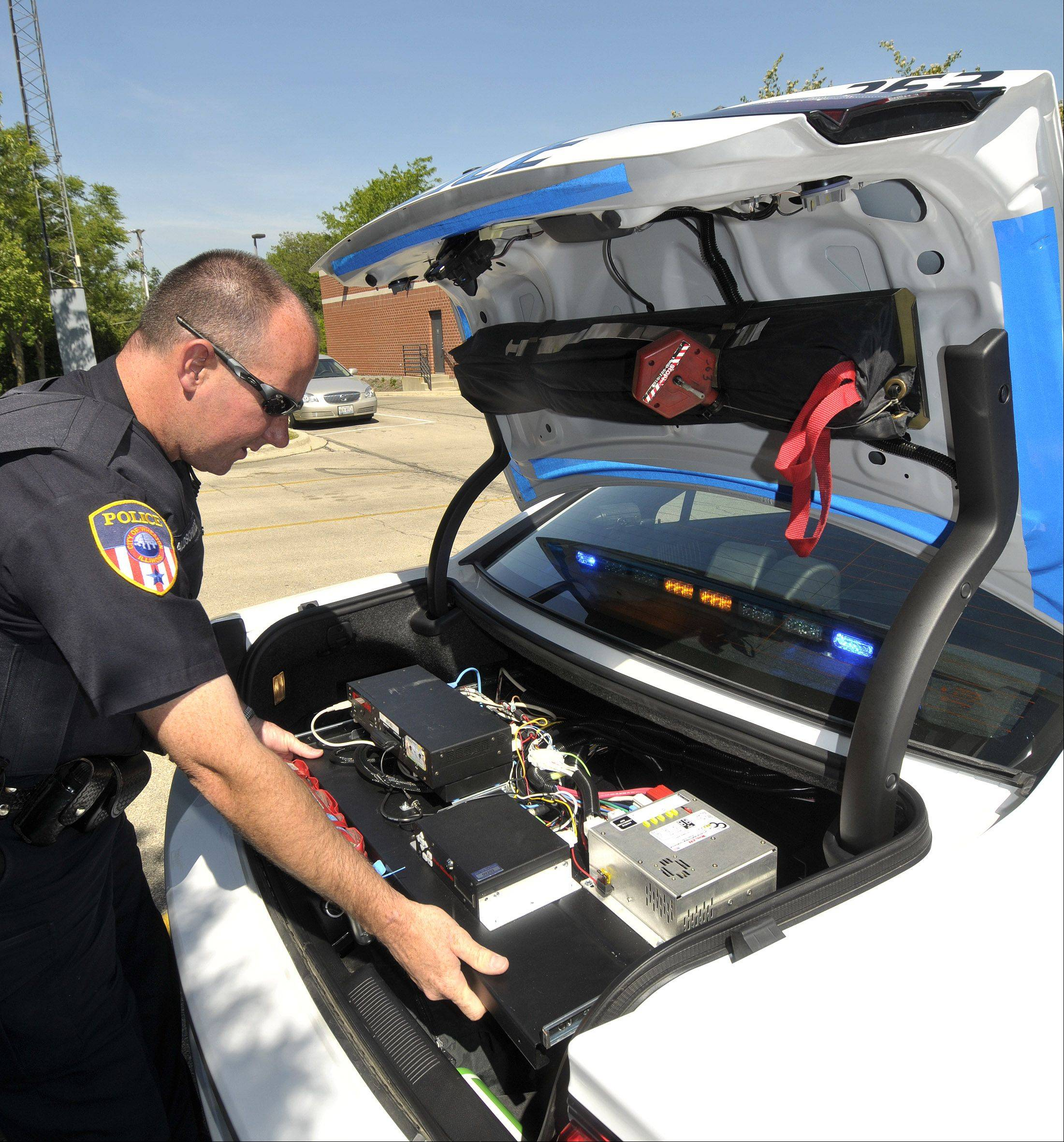 Wheaton police officer Neil Waldschmidt shows how the 2-way radio equipment in the trunk is on a slide out tray which makes it easier and faster for the radio technicians to get at the gear for repairs.