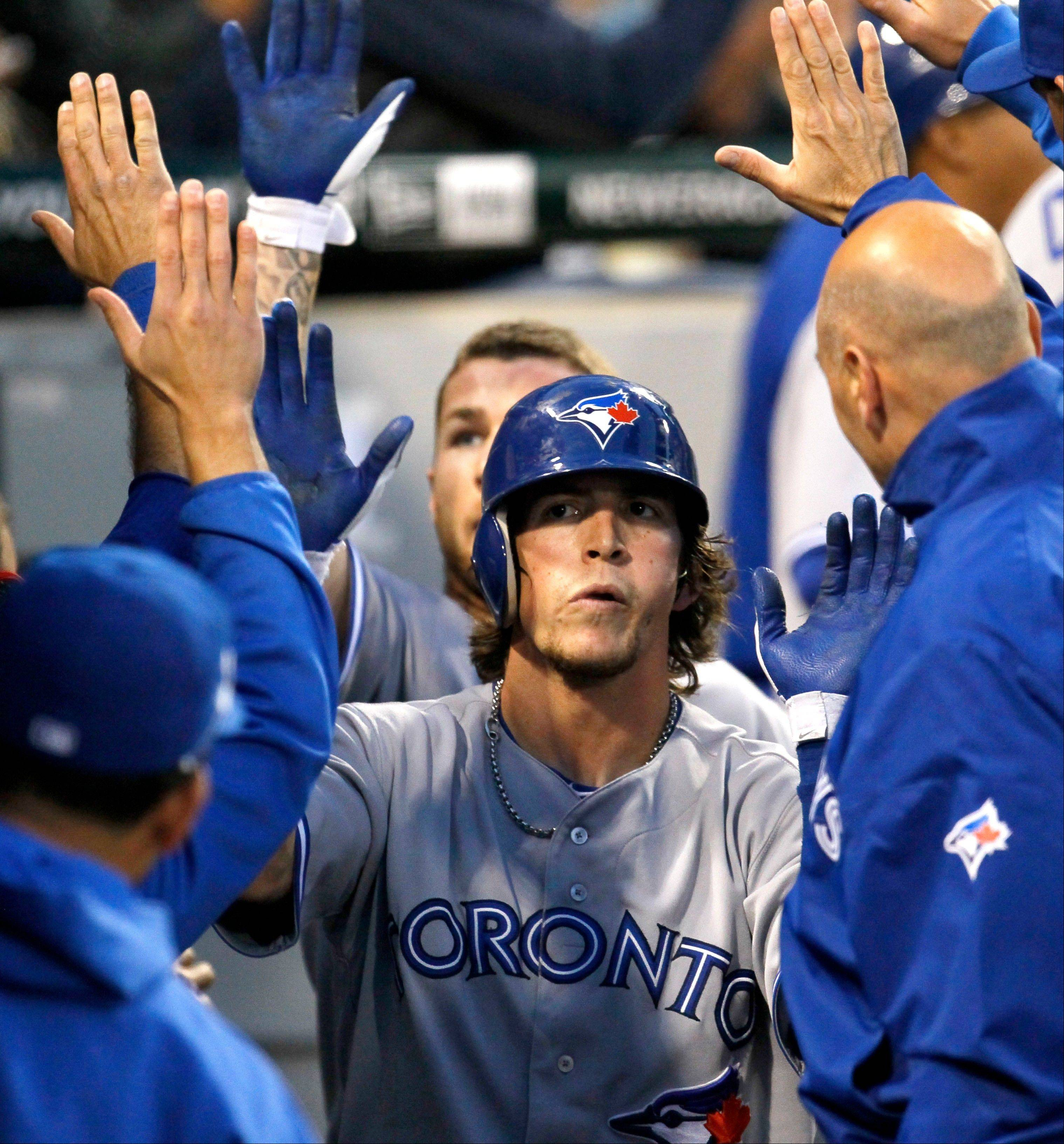 The Blue Jays' Colby Rasmus is greeted in the dugout after hitting the first of a pair of 2-run homers off White Sox starting pitcher Philip Humber in the fifth inning Tuesday night.