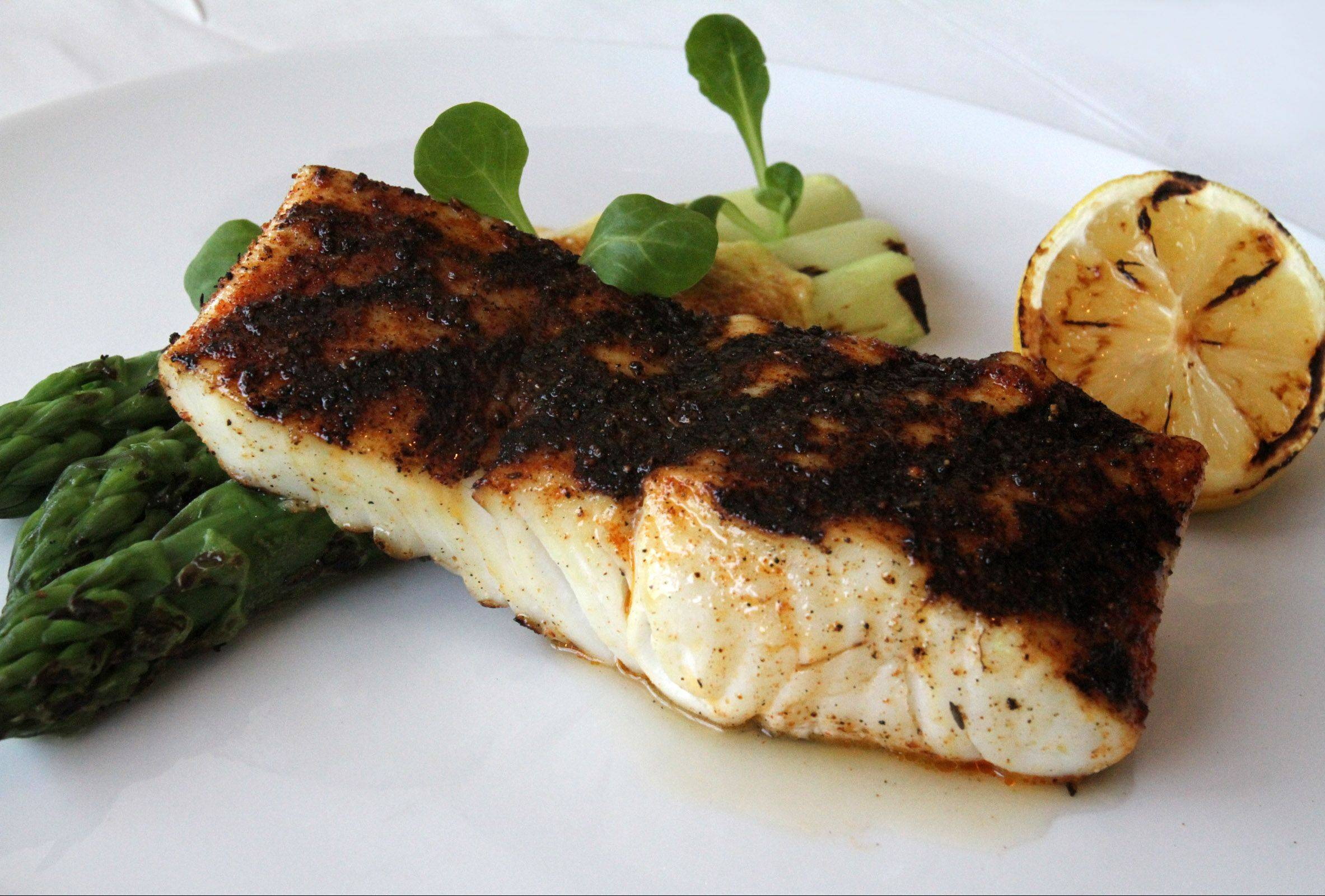 Chef James Papadopoulus hits halibut with a heavy dose of homemade blackening seasoning before the fillets hit the grill at Sam and Harry's at the Renaissance Convention Center in Schaumburg.