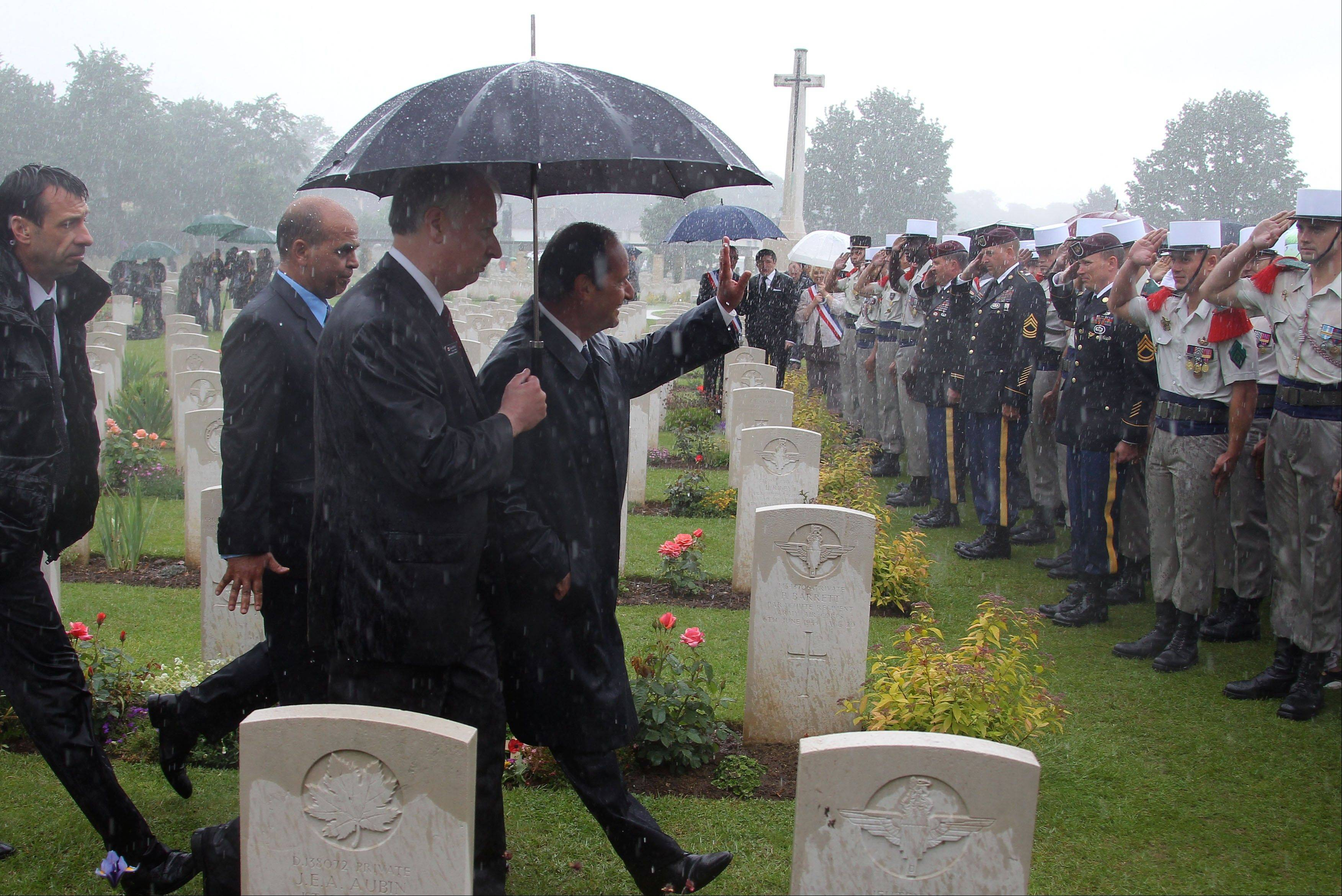 French President Francois Hollande waves to soldiers at the end of a ceremony commemorating the 68th anniversary of the D-Day invasion of France began in 1944, in the British war cemetery of Ranville, western France, Wednesday, June 6, 2012.