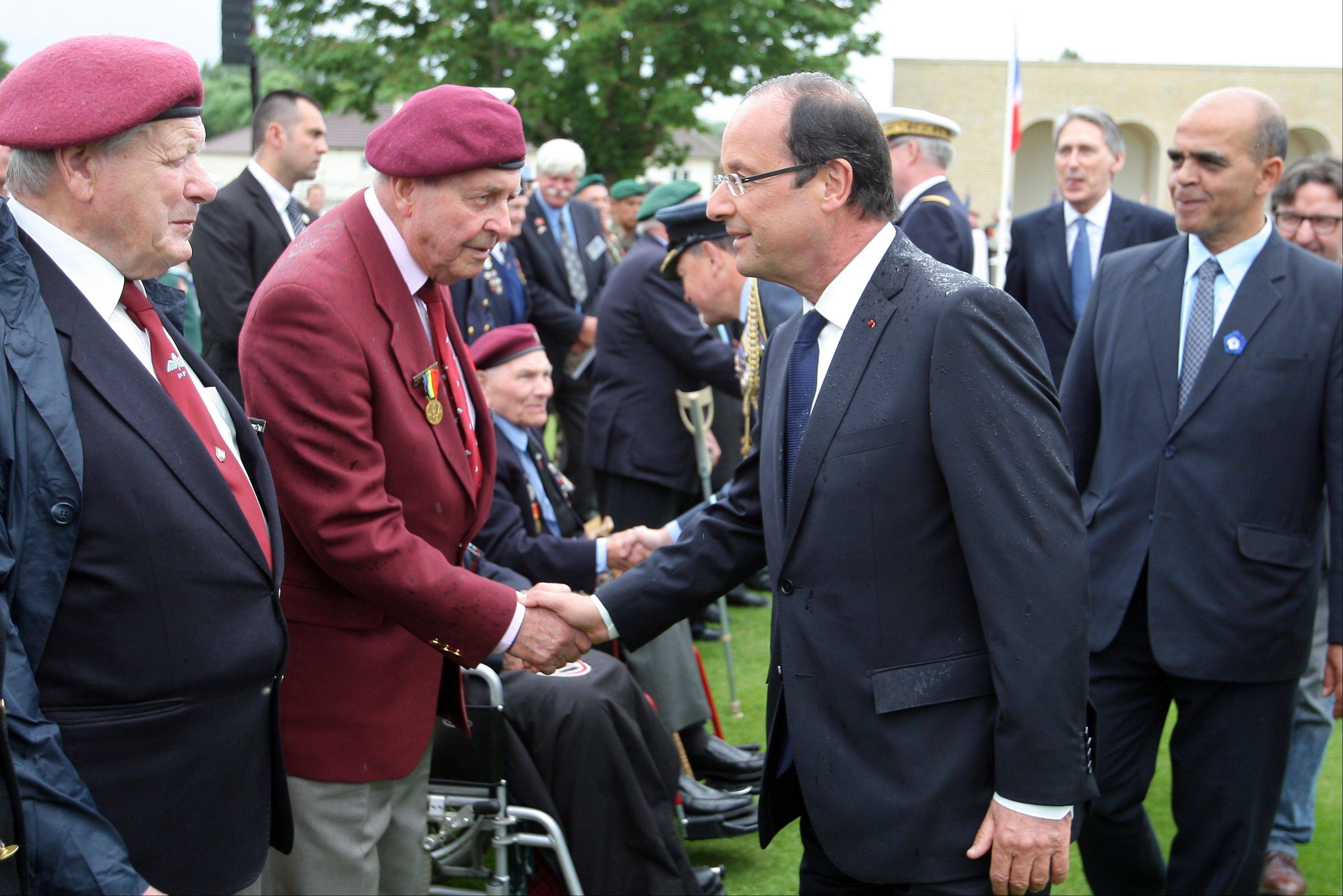 French President Francois Hollande shakes hands with WWII veterans during a ceremony commemorating the 68th anniversary of the D-Day invasion of France began in 1944, in the British war cemetery of Ranville, western France, Wednesday, June 6, 2012.