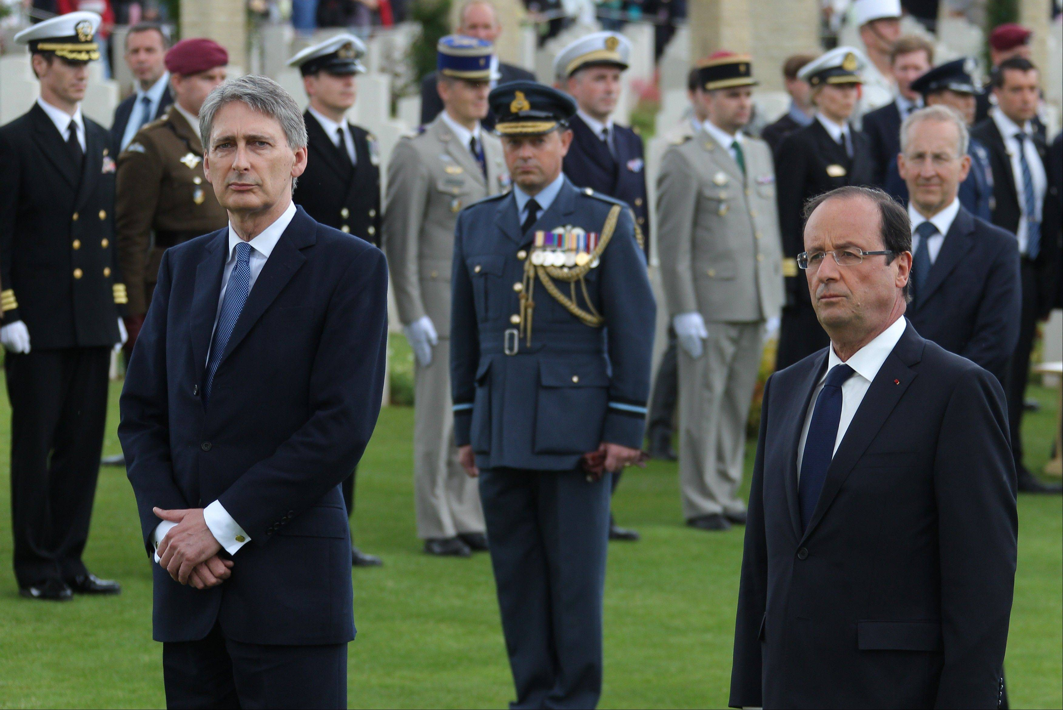 French President Francois Holland, right, and British Defense Ministry Philippe Hammond, left, take part a ceremony commemorating the 68th anniversary of the D-Day invasion of France began in 1944, in the British war cemetery of Ranville, western France, Wednesday, June 6, 2012.