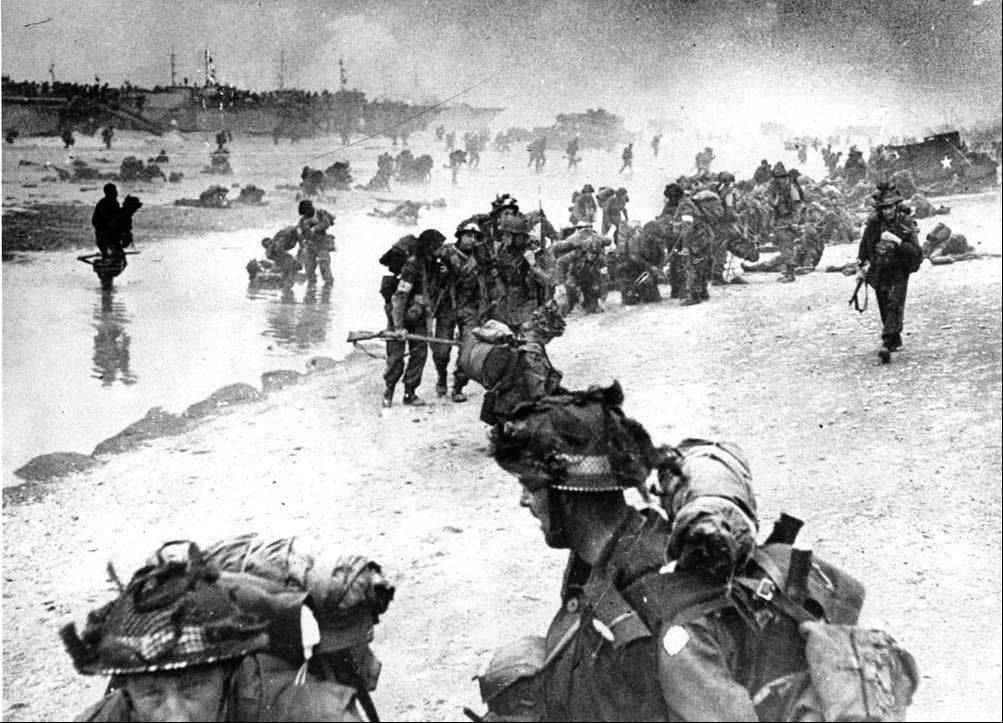 Wounded British troops from the South Lancashire and Middlesex regiments are helped ashore at Sword Beach