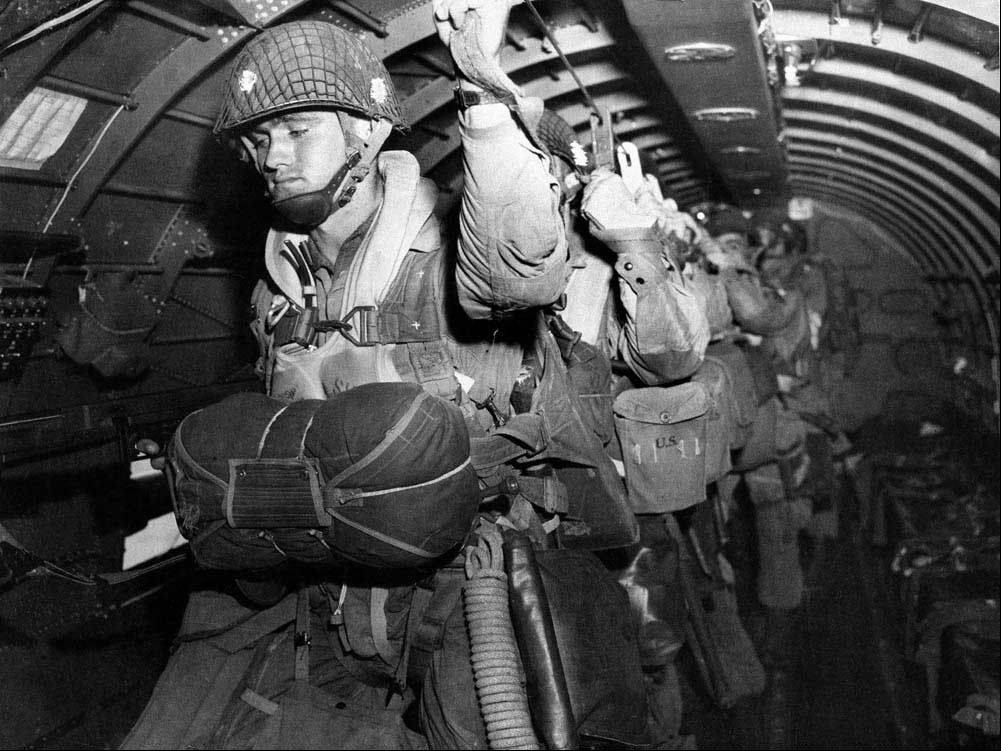 U.S. paratroopers fix their static lines before a jump before dawn over Normandy.