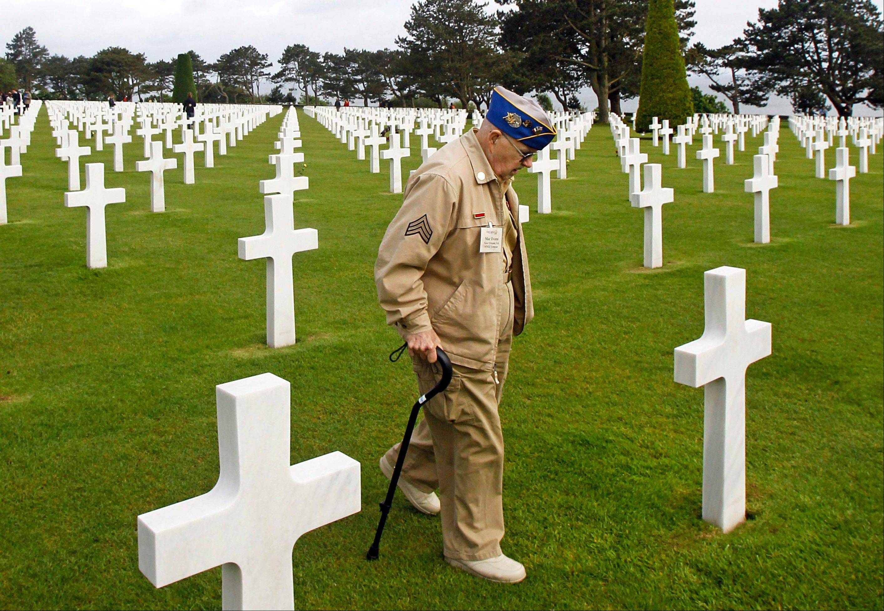 U.S. WW II veteran Clarence Mac Evans, 87, from West Virginia, who landed in Normandy on June 6, 1944, with the 29th infantery division, walks among the graves at the Colleville American military cemetery, in Colleville sur Mer, western France, Wednesday June 6, 2012, before the start of the ceremony commemorating the 68th anniversary of the D-Day. Clarence MacEvans is searching for the tombs of 17 of his fellows who died on D Day.