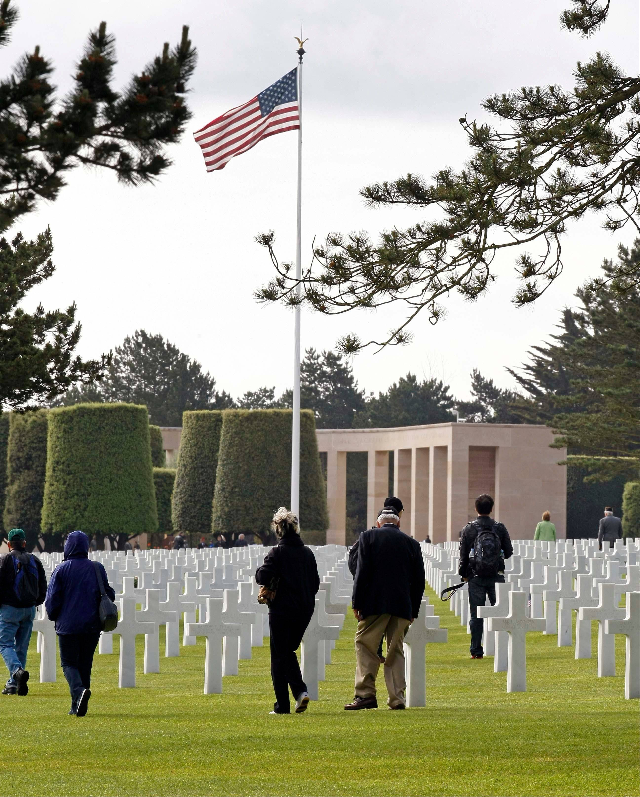 Visitors walk among tombs at the Colleville American military cemetery, in Colleville sur Mer, western France, Wednesday June 6, 2012, as part of the commemoration of the 68th anniversary of the D-Day.