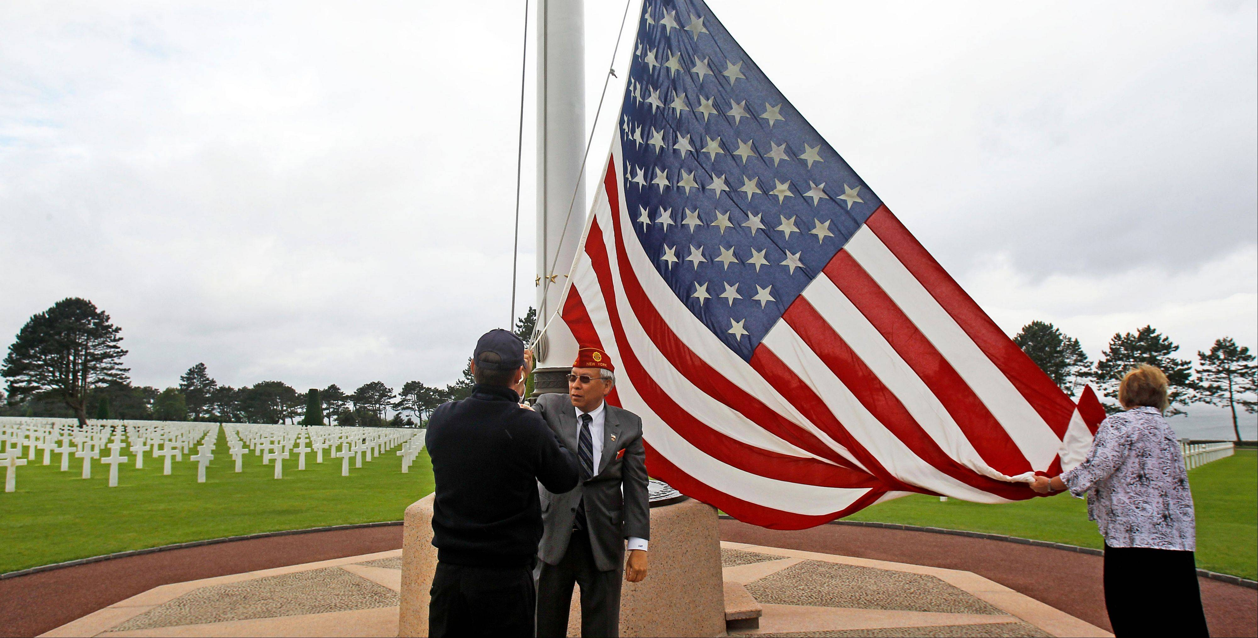 The U.S. flag is being raised at the Colleville American military cemetery, in Colleville sur Mer, western France, Wednesday June 6, 2012, before the start of the ceremony commemorating the 68th anniversary of the D-Day.