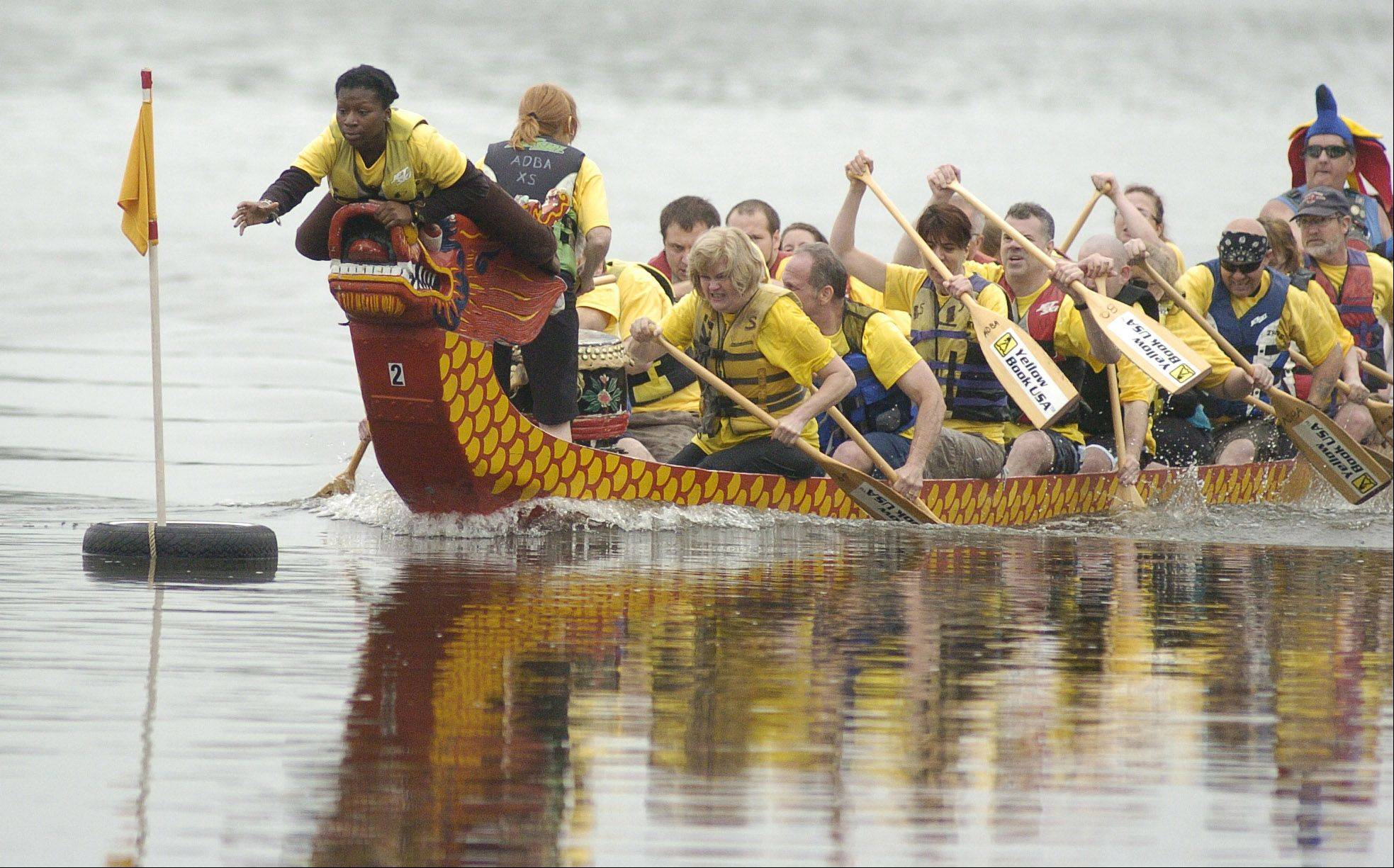 Siessourby Soma, 17, of Evanston grabs the flag for her team, the World Dragons, to win the first of two heats during dragon boat races during the Pride of the Fox RiverFest in St. Charles last year.