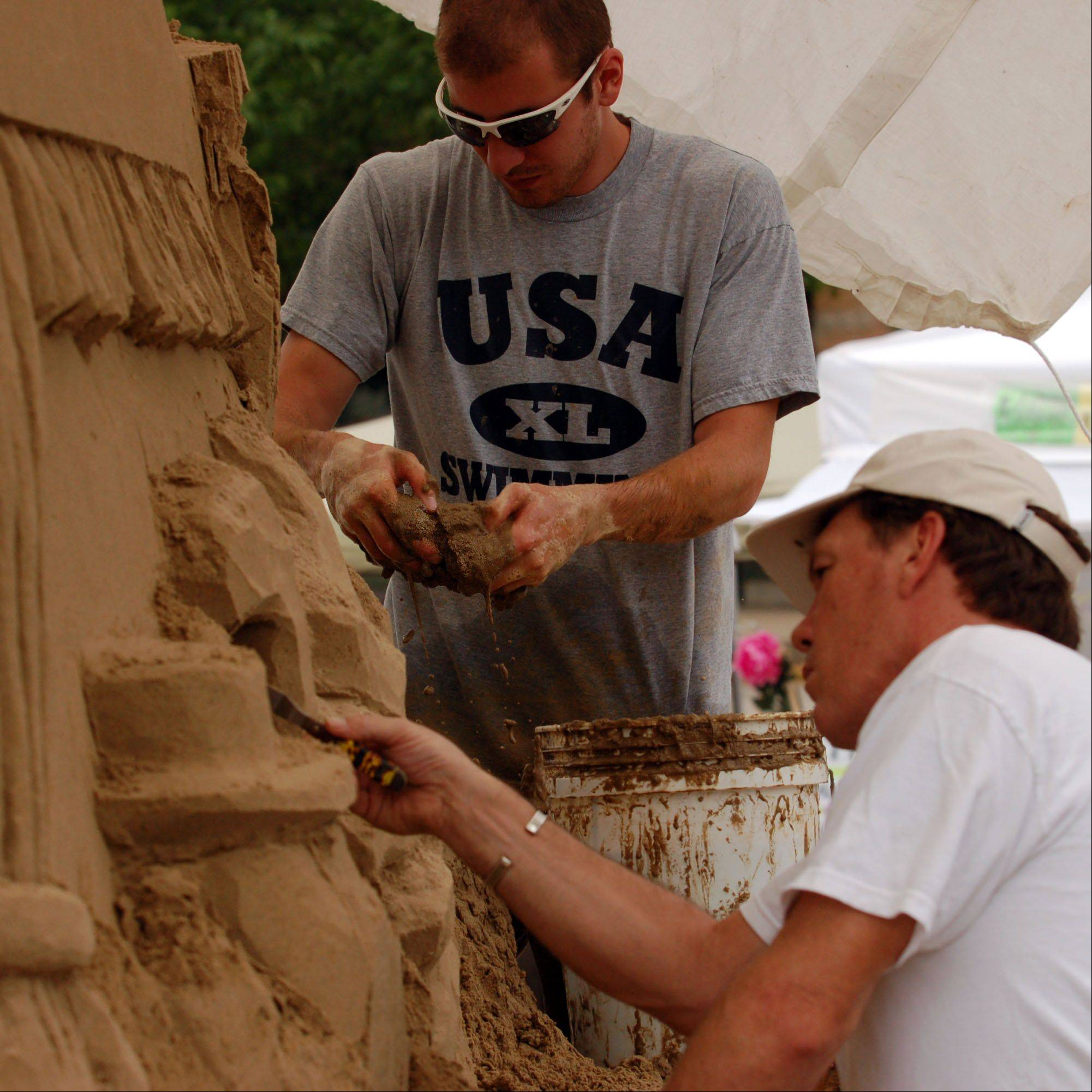 Buck Hoover of Woodstock, center, of The Sand Sculpture Company assists experienced sculptor Charlie Beaulieu of Woodstock, right, as they construct a work for last year's Pride of the Fox RiverFest festival. The company travels all around the world creating custom sand sculptures and sand castles for all types of events.