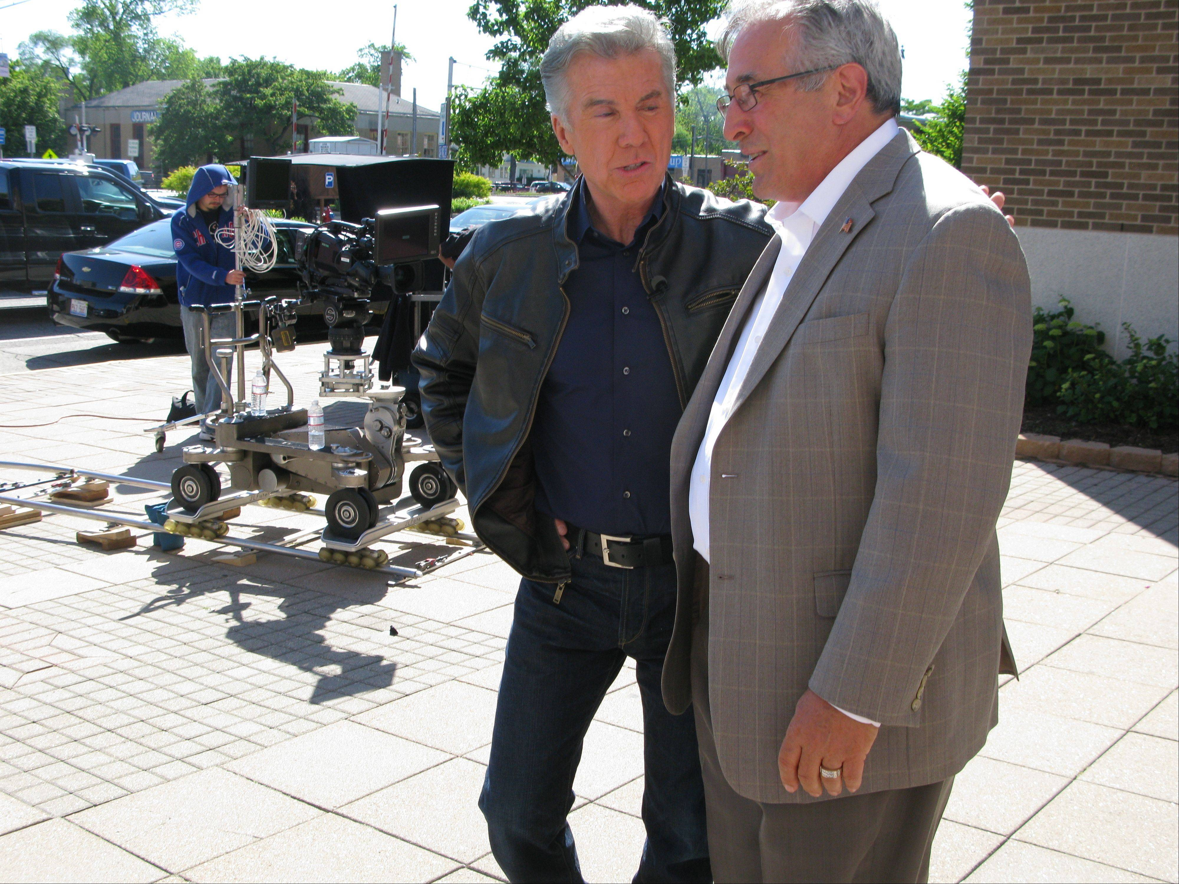 "John Walsh, host of ""America's Most Wanted,"" talks with Des Plaines Mayor Marty Moylan during the filming."
