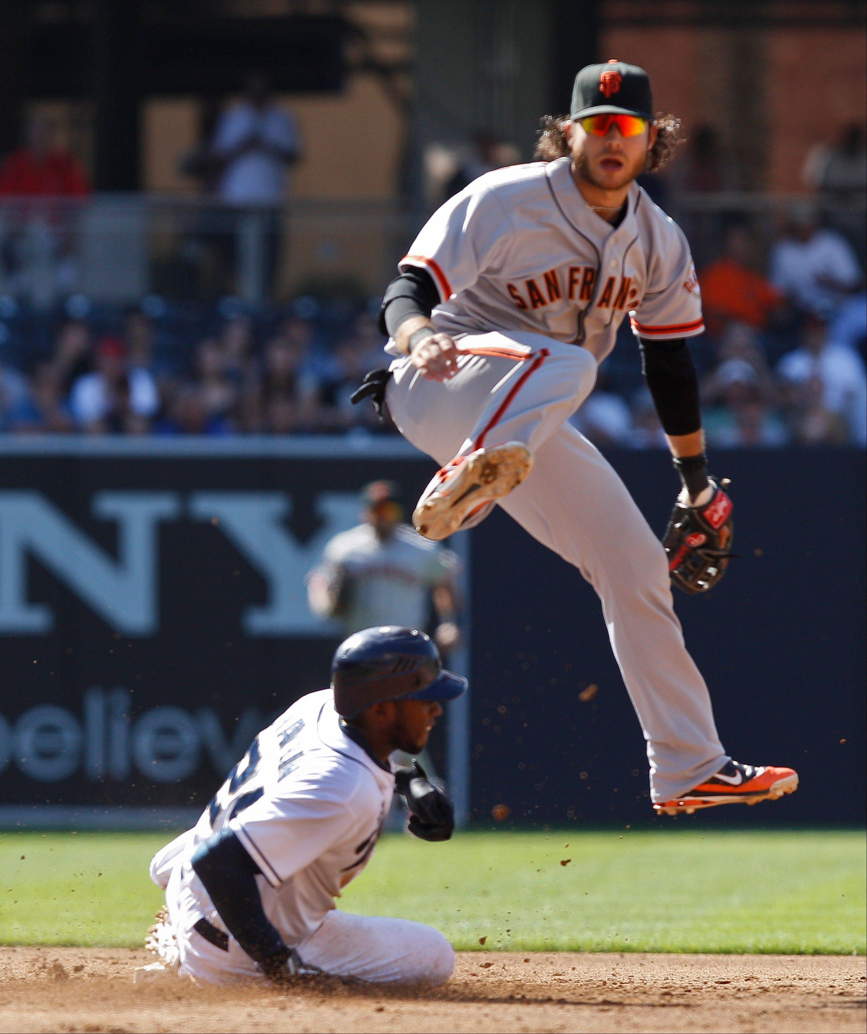 San Francisco Giants shortstop Brandon Crawford hurdles the San Diego Padres' Cameron Maybin while relaying to first to complete a double play Wednesday during the third inning in San Diego.