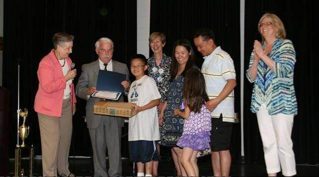 Thomas Tran and his family receive a mini-laptop computer and a certificate of award for his placement in the Foundation for Investor Education's InvestWrite essay competition.