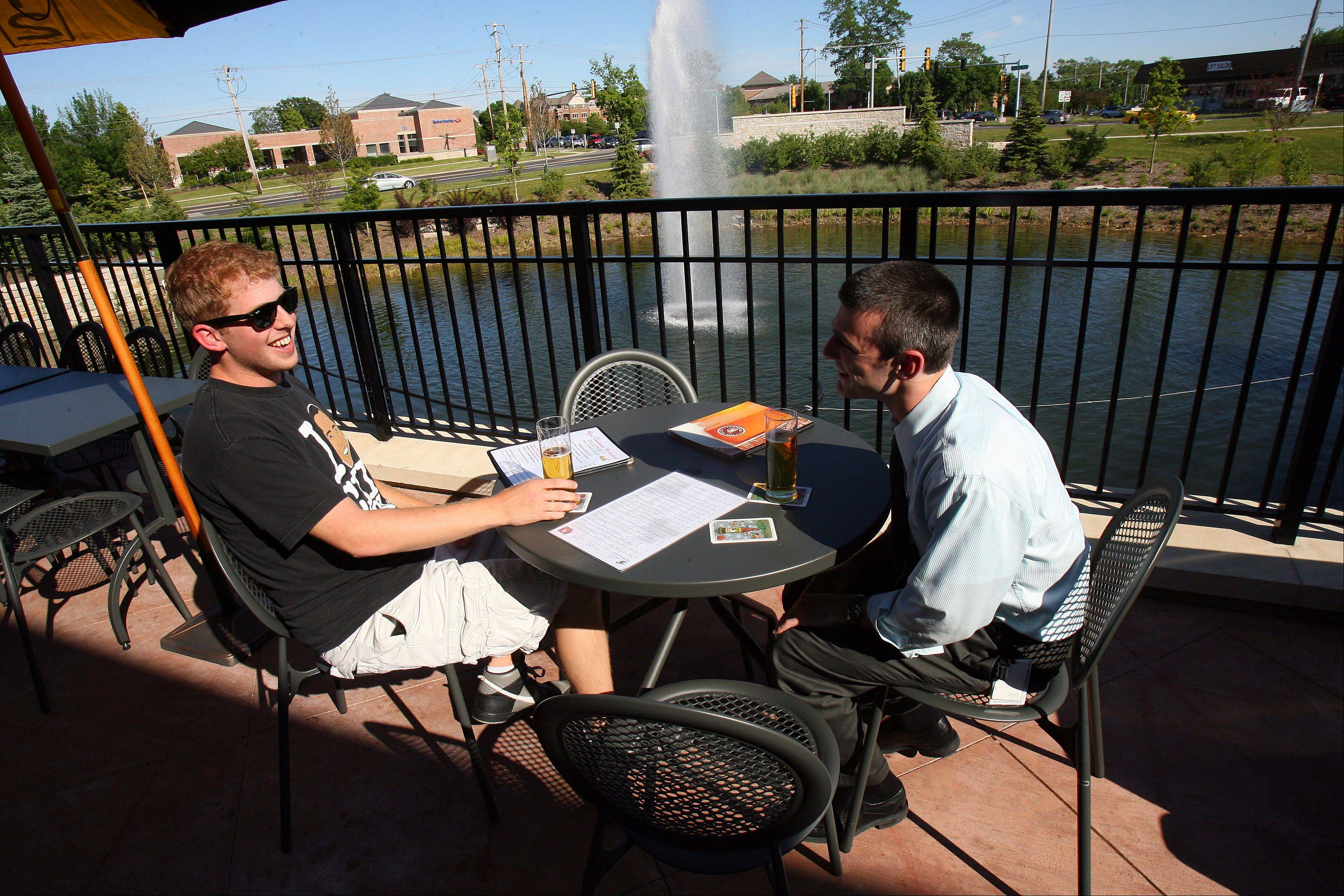 Ben Gleicher, left, and Mark Levitt, both of Buffalo Grove, enjoy a beer on the patio at the Beer Market in Vernon Hills.