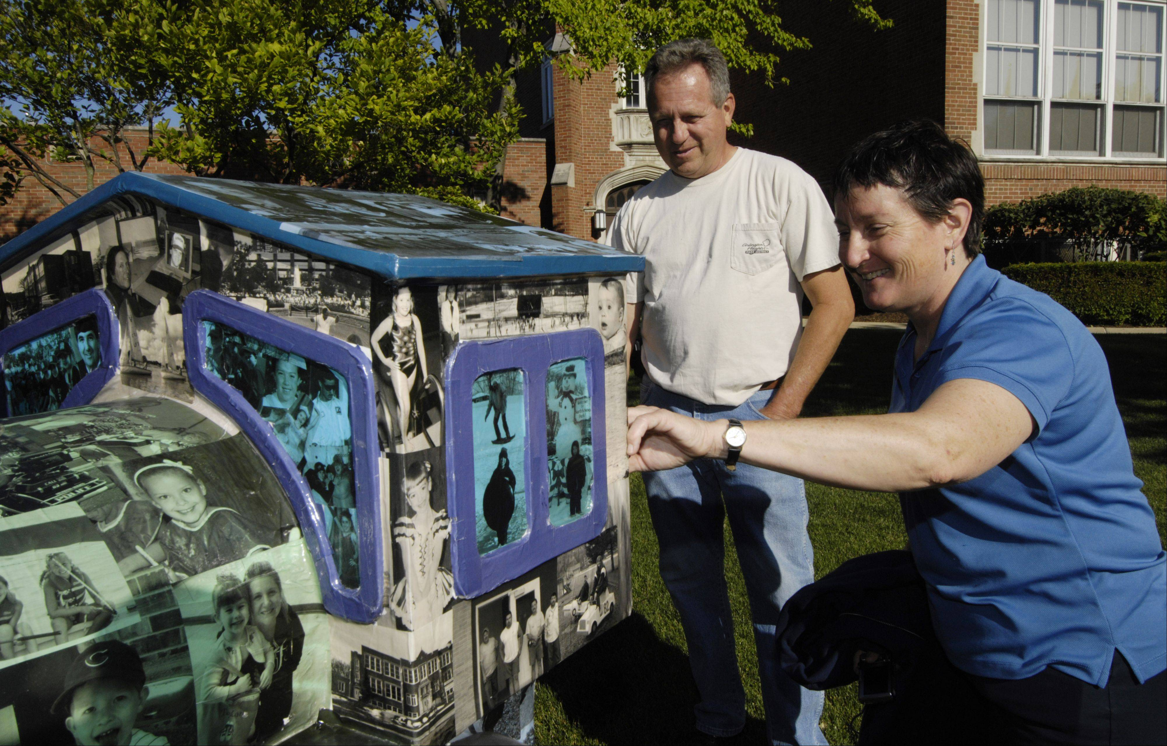 Pat Klawitter, right, chairman of the Arlington Heights Park District's morale committee, and Rich Knox, parks department staff member, talk about photos decorating the district's train for the village's 125th anniversary.