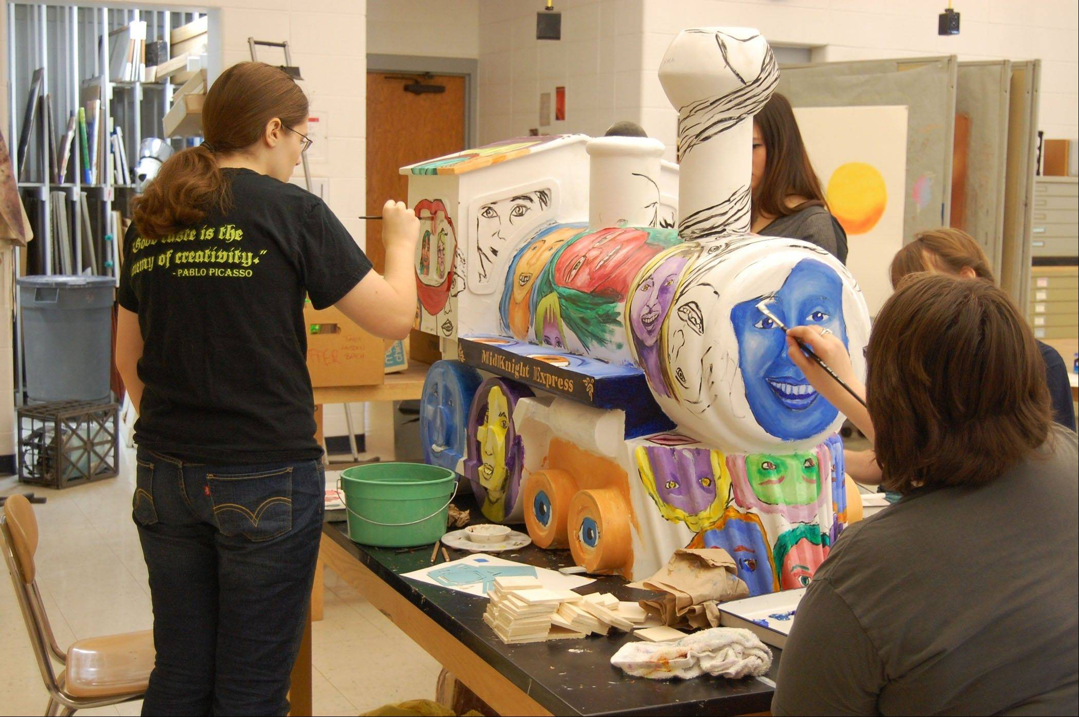 Prospect High School students paint the Mid Knight Express. for Bradish Associates. The train will be on display outside the company's office, 215 N. Arlington Heights Road, as part of Arlington Heights celebration of its 125th anniversary.