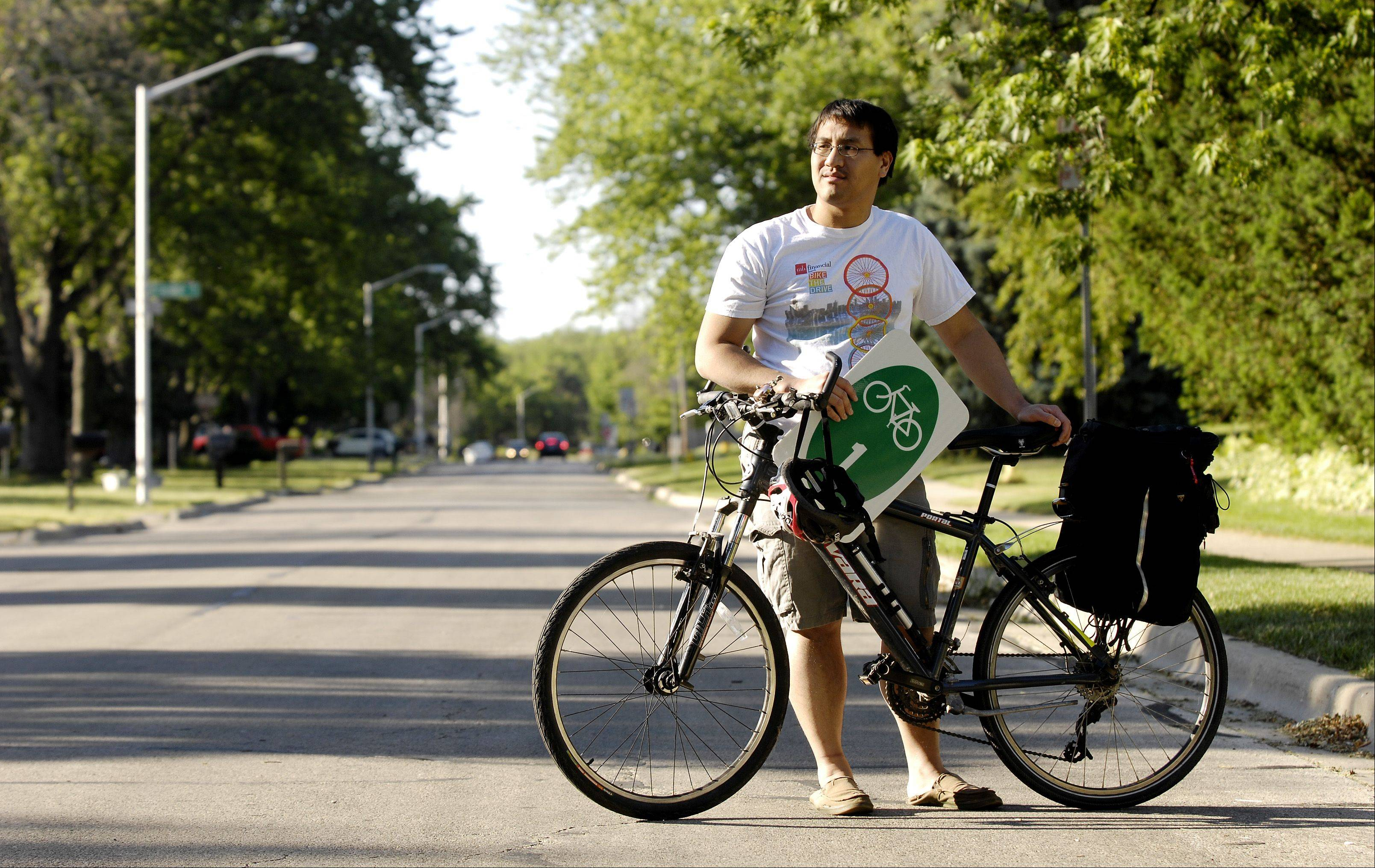 "Robert Guico of Carol Stream has proposed placing bike route signs on village streets as one way to promote a ""friendlier"" environment for bicyclists. But village officials say his proposal isn't comprehensive enough."