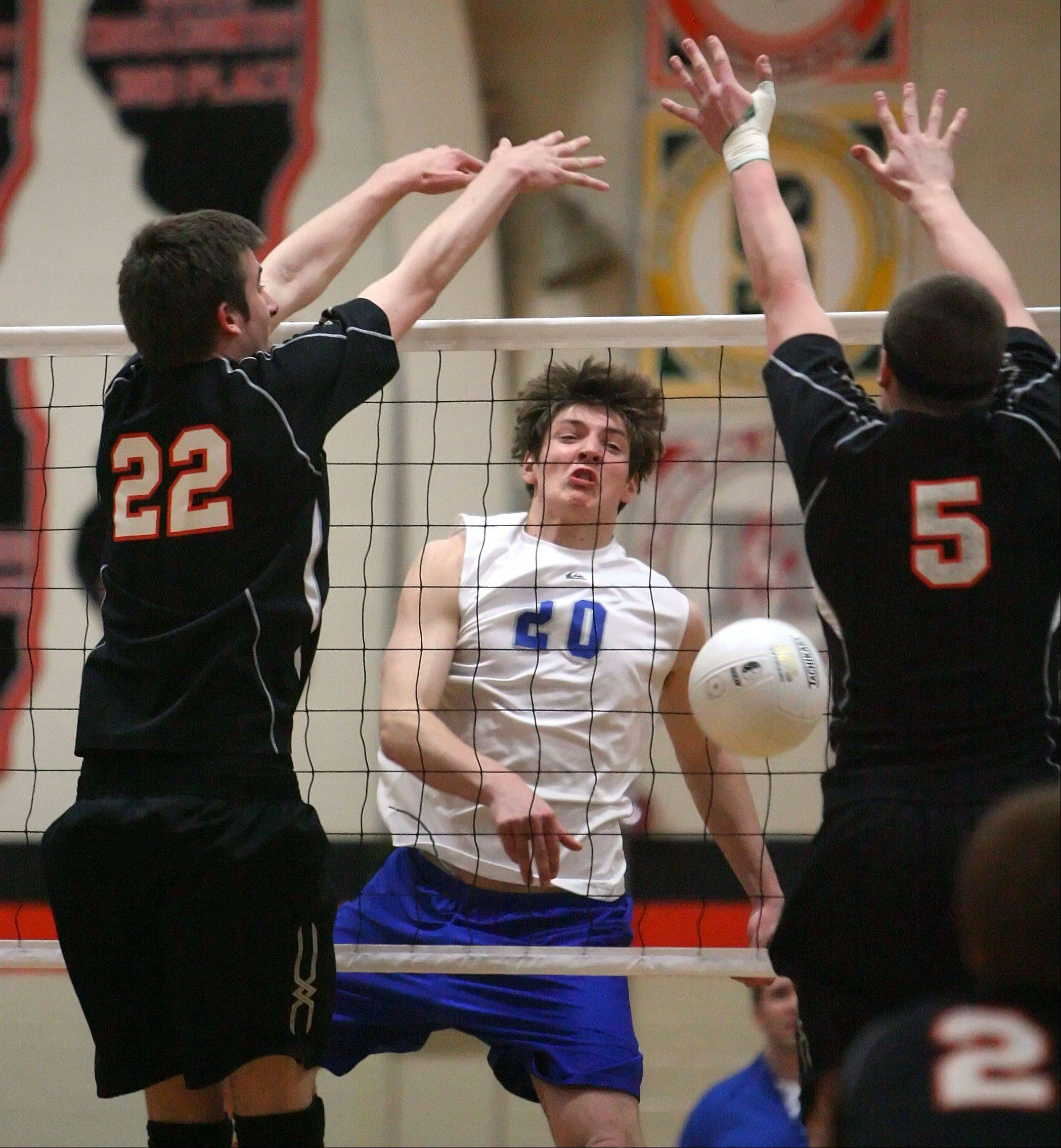 Vernon Hills' Martin Niemczewski, center, spikes one against Libertyville.