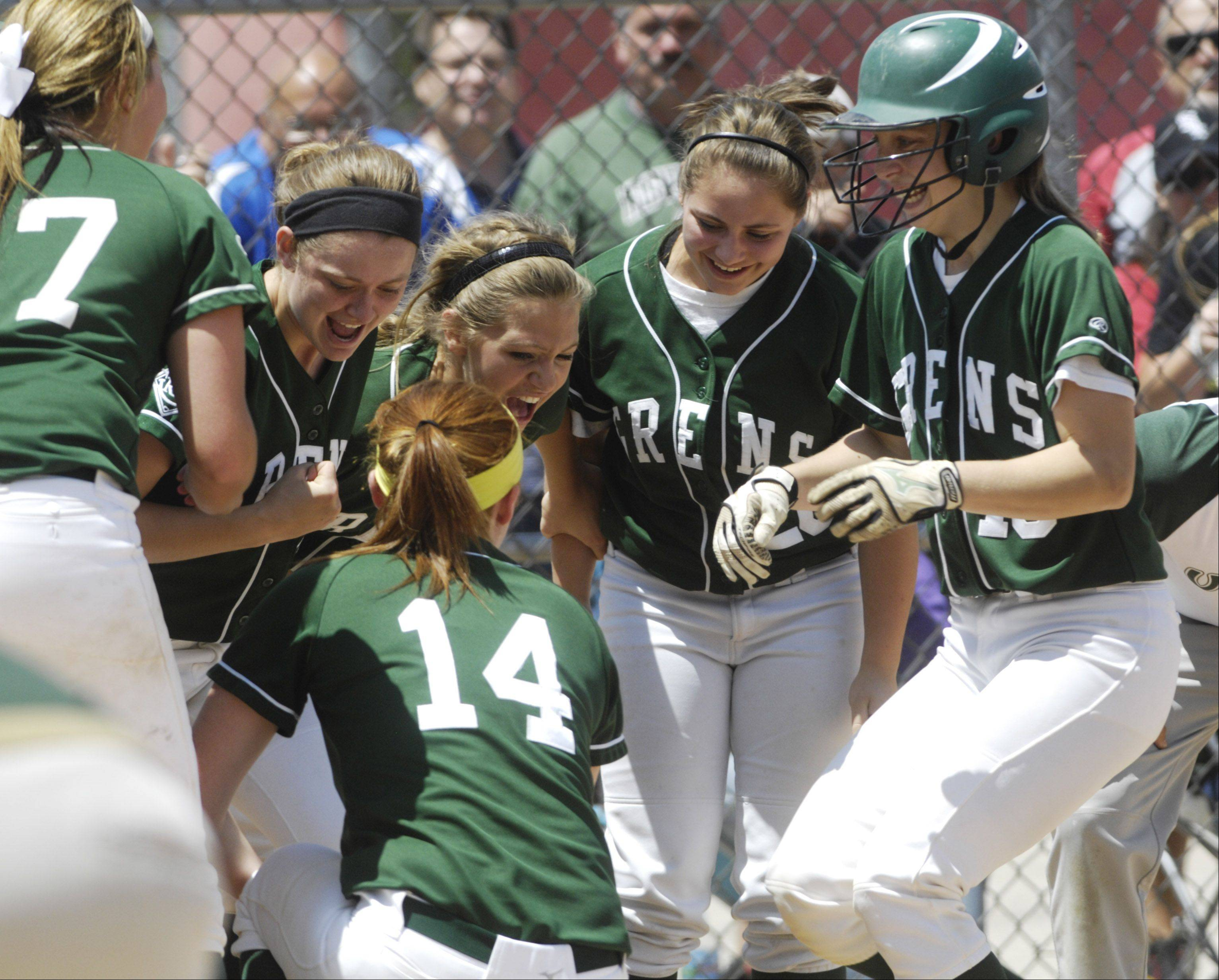Elk Grove's Devan Parkison, right, is greeted at the plate by her teammates after her eighth-inning home run gave the Grens the lead over Conant during Saturday's sectional final at Barrington.