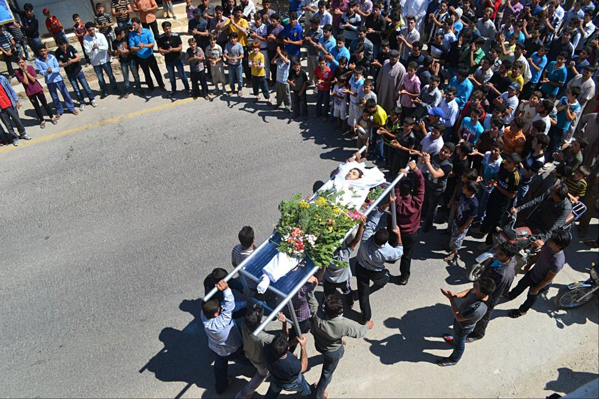 This citizen journalism image provided by Edlib News Network ENN, purports to show anti-Syrian regime mourners carrying the dead body of Thaer al-Khatib during his funeral procession, at the northern town of Kfar Nebel, Syria, Friday. Thaer al-Khatib was killed by Syrian security forces.