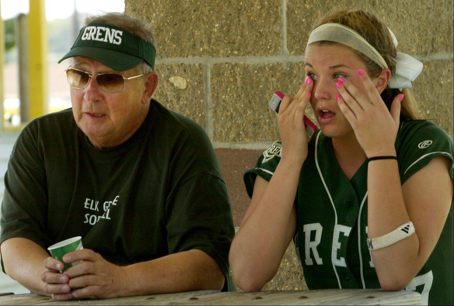 Elk Grove's Dani Goranson, with coach Ken Grams, wipes away tears after the Grens' loss to Marist in the Class 4A softball state semifinals.