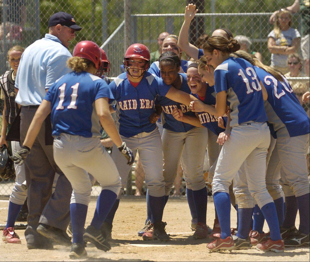 Jane Trzaska (11) is about to be mobbed after hitting a 2-run homer in the fourth inning to give Glenbard South a 6-1 lead over Mattoon during the Class 3A state softball semifinals Friday in East Peoria.