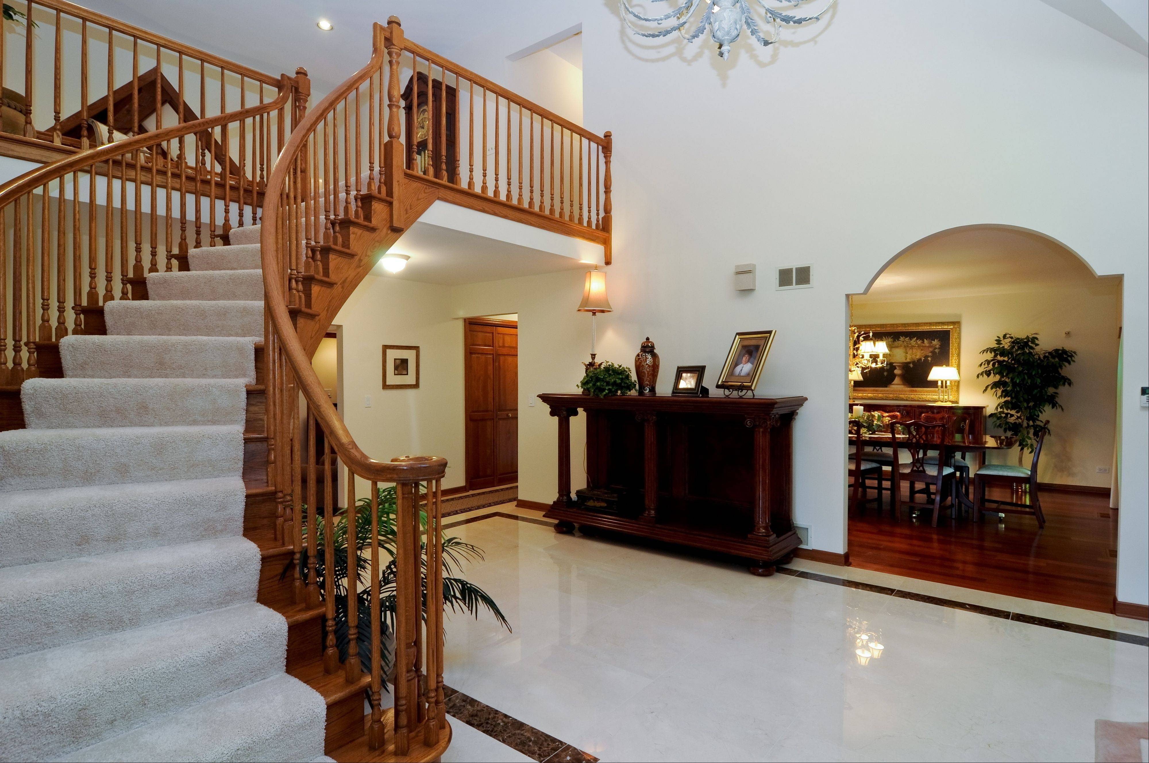 Visitors to this home are greeted by a grand, two-story marble foyer.