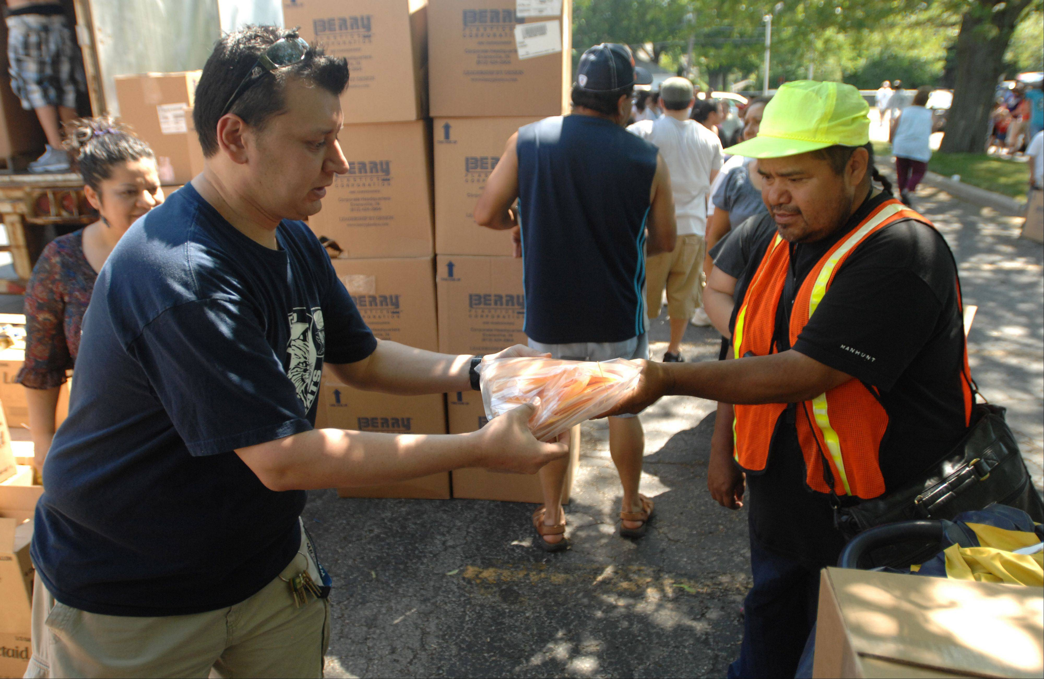 "Bill Bautista of Bloomingdale hands a bag full of cheese slices to Jose Jurado of West Chicago during a ""Rescue the Food"" event outside West Chicago Community High School Saturday. Volunteers gave away some 80,000 pounds of food to about 500 people."