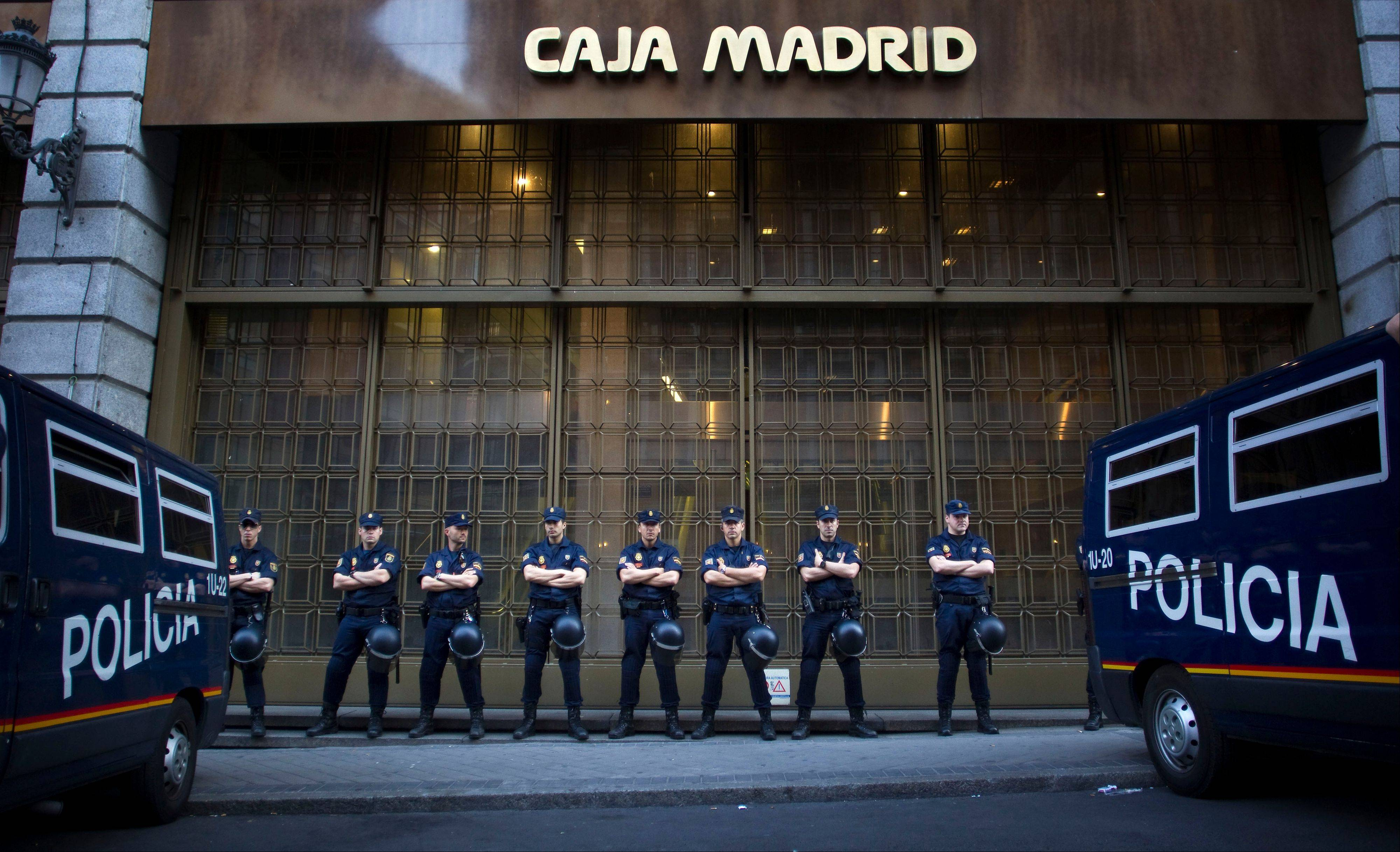 Riot police stand guard in front of a branch of the recently nationalized Caja de Madrid/Bankia bank during a protest in Madrid. Spain asked for a European rescue of its troubled banks Saturday.