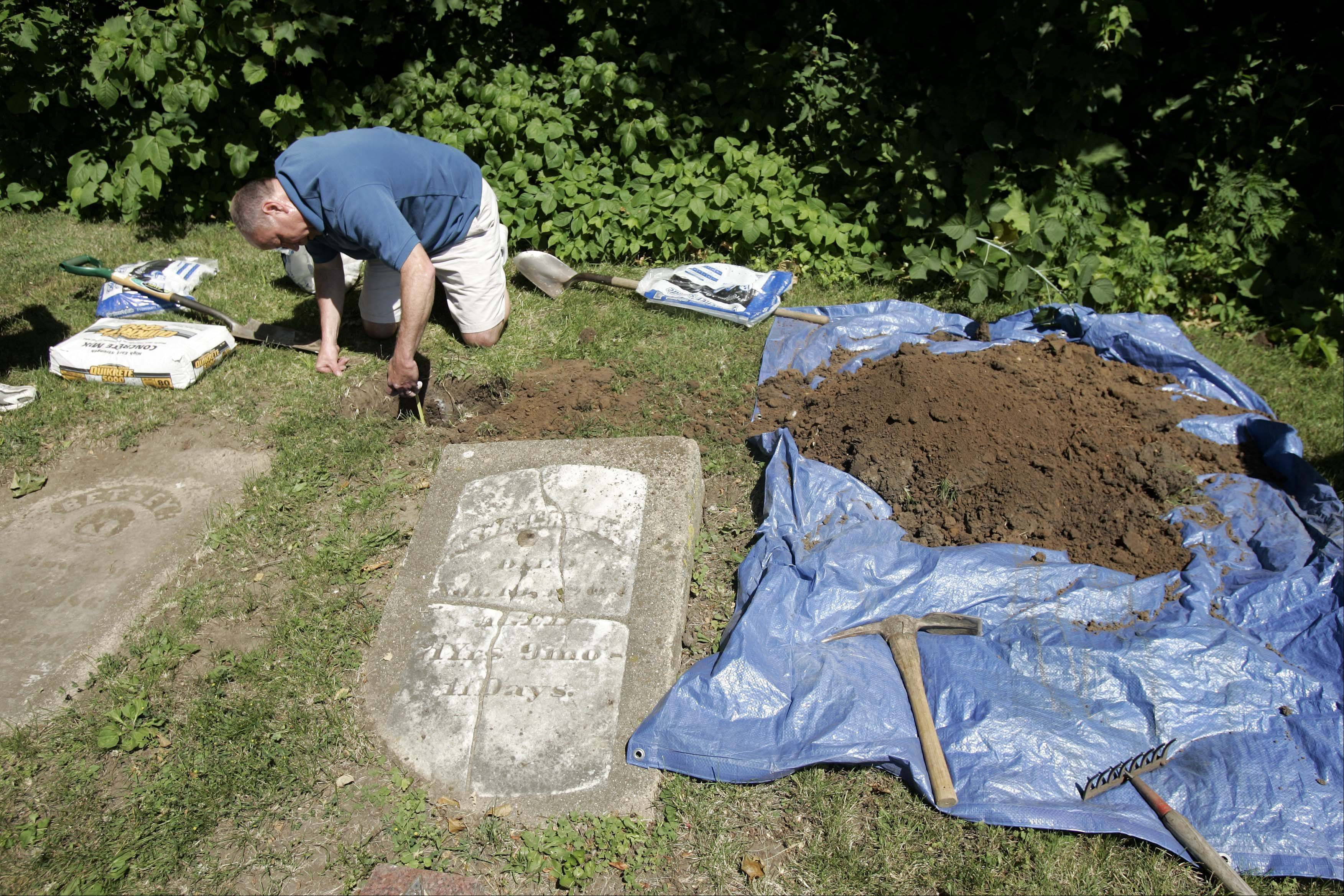 Mike Rowley checks the depth of the hole before installing the new headstone.