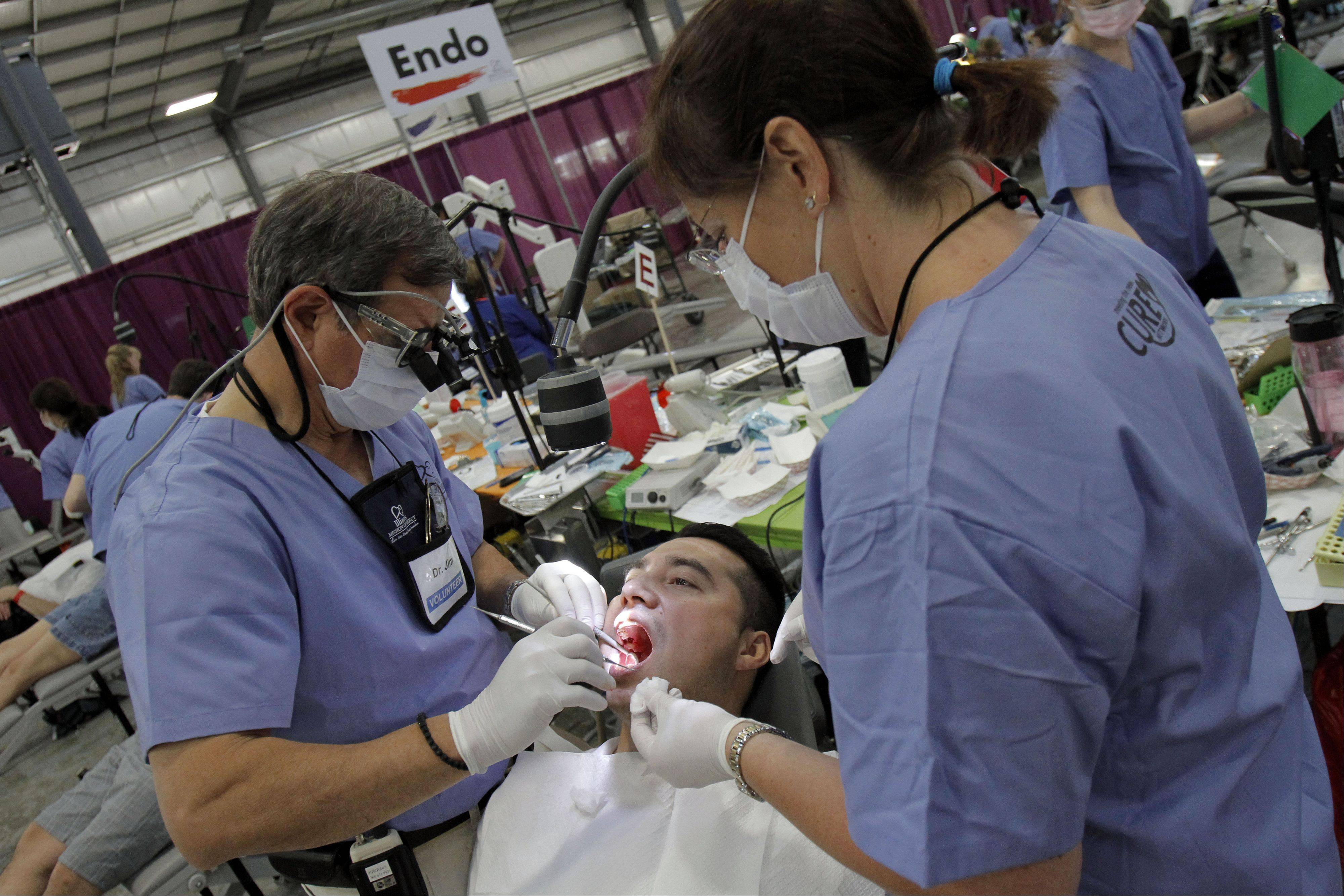 Rojelia Reyes of Waukegan has some dental work done Friday by Dr. Jim Maragos, left, and hygienist Barbara Cervantes at the Lake County Fairgrounds in Grayslake. Volunteers expected to provide an estimated $1 million in free medical, dental and vision care through today during what's called the Mission of Mercy.
