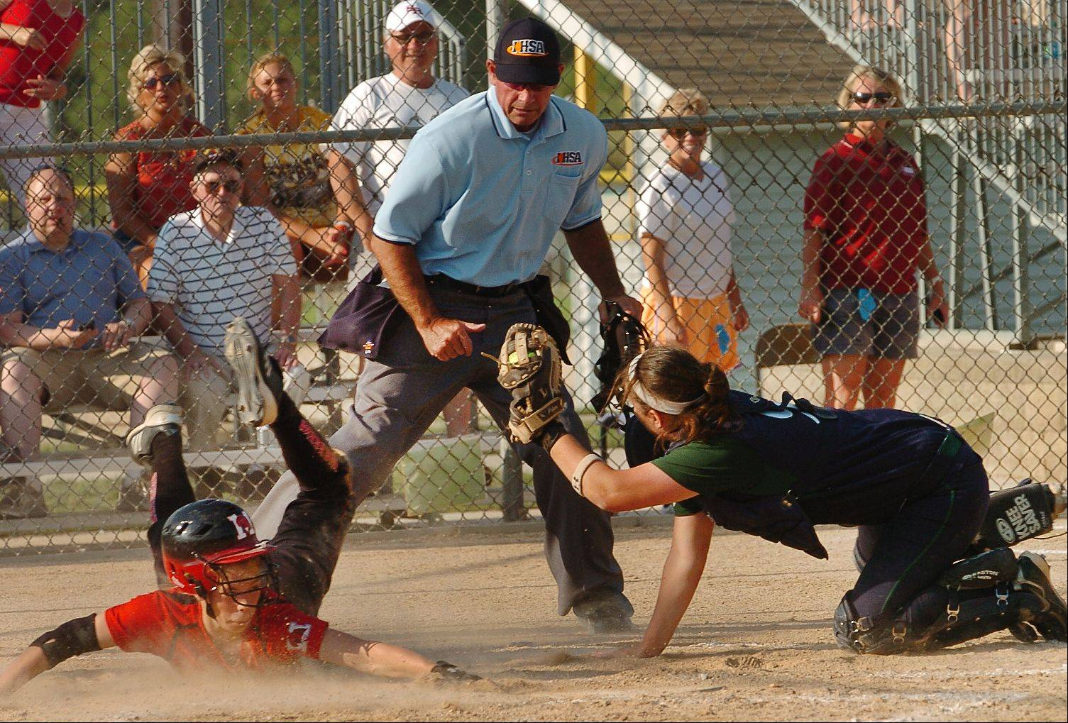 Bartlett catcher Kaylyn Zierke holds on to the ball after tagging out Marist's Nicole Babrowski at the plate in the first inning of the Class 4A softball state championship game between Bartlett and Marist.