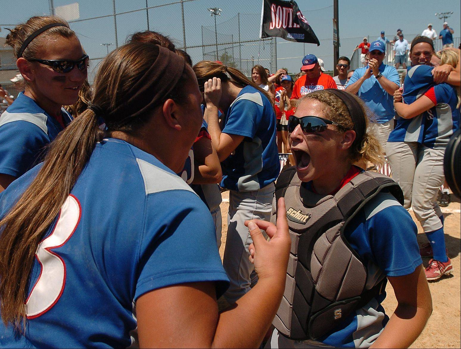 Olivia Ramirez, left, and Jane Trzaska celebrate after Glenbard South captures the class 3A state softball championship.