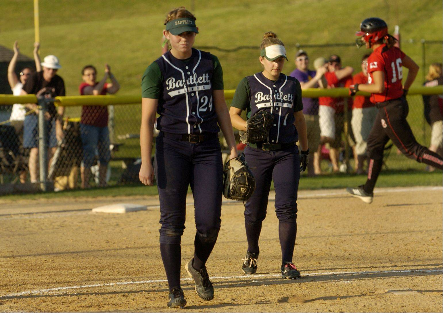 Marist's Haley Richy circles the bases, far right, behind a dejected Tori Burke, after hitting a grand slam in the 5th inning during Class 4A state softball championship game .