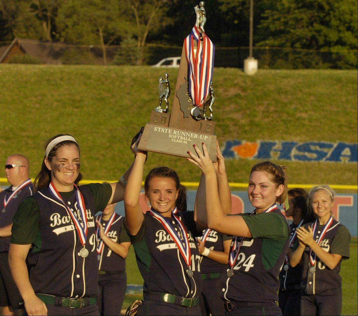 Kaylyn Zierke, Amanda Montbriand and Tori Burke hoist the 2nd place Class 4A state softball championship trophy after losing to Marist.