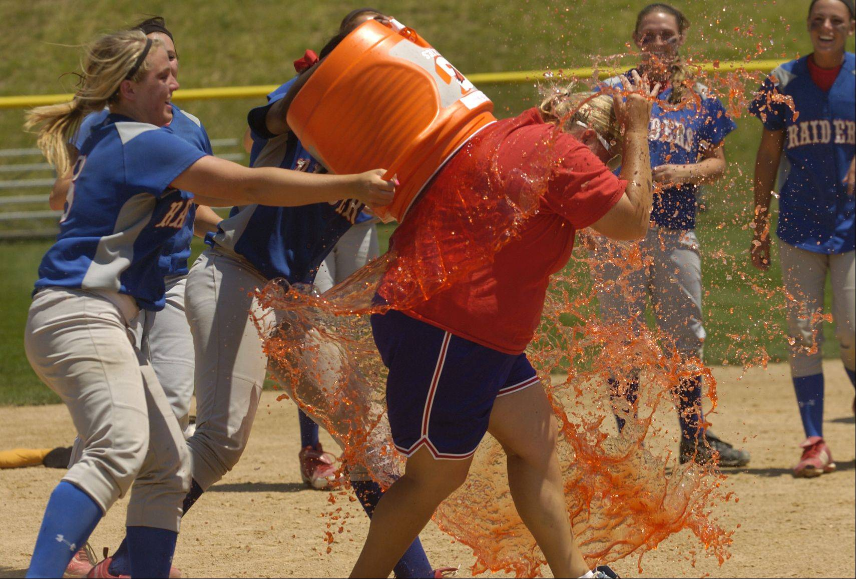 Assistant coach Kris Morton gets a Gatorade bath after Glenbard South wins the Class 3A state softball championship.