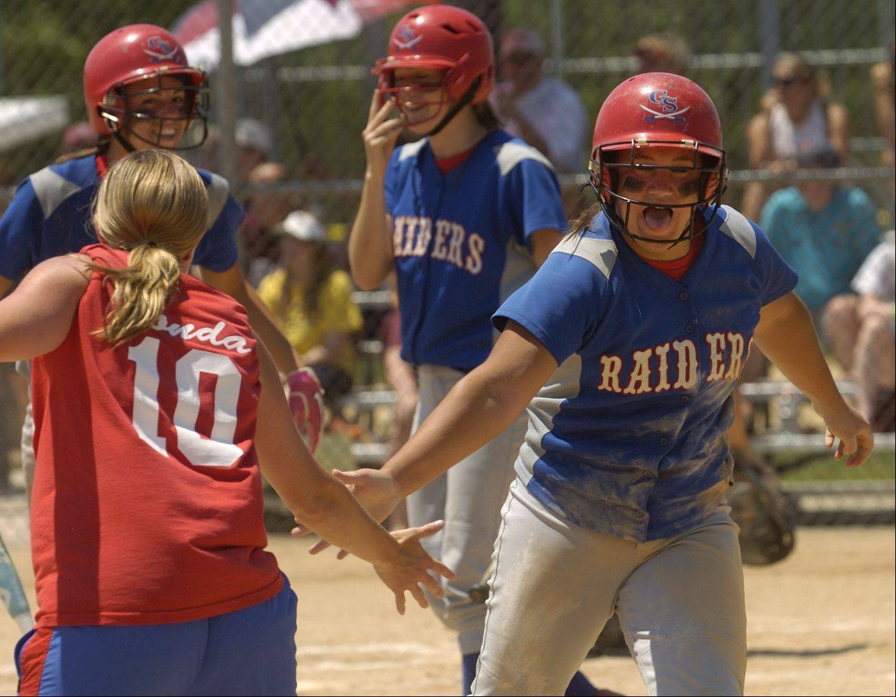 Glenbard South's Olivia Ramirez is congratulated by coach Julie Fonda after scoring first of 2 Raiders runs in the fourth inning of the Class 3A softball state final against Marengo.
