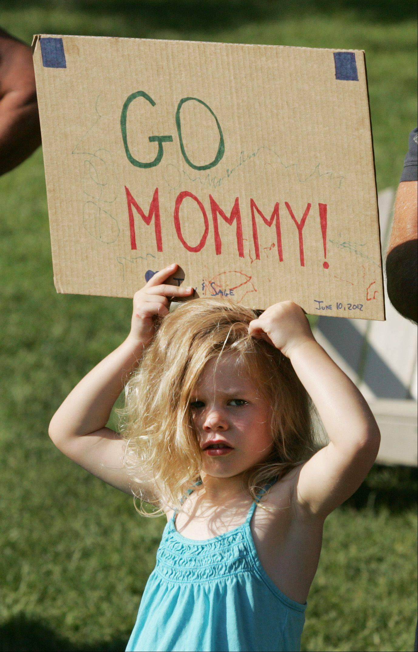 Ivy Riordan, 3, of St. Charles supports her mother Anne, during the SheROX Triathlon in Naperville. The event featured a .75-kilometer swim, 22.8-kilometer bike ride and 5-kilometer run..