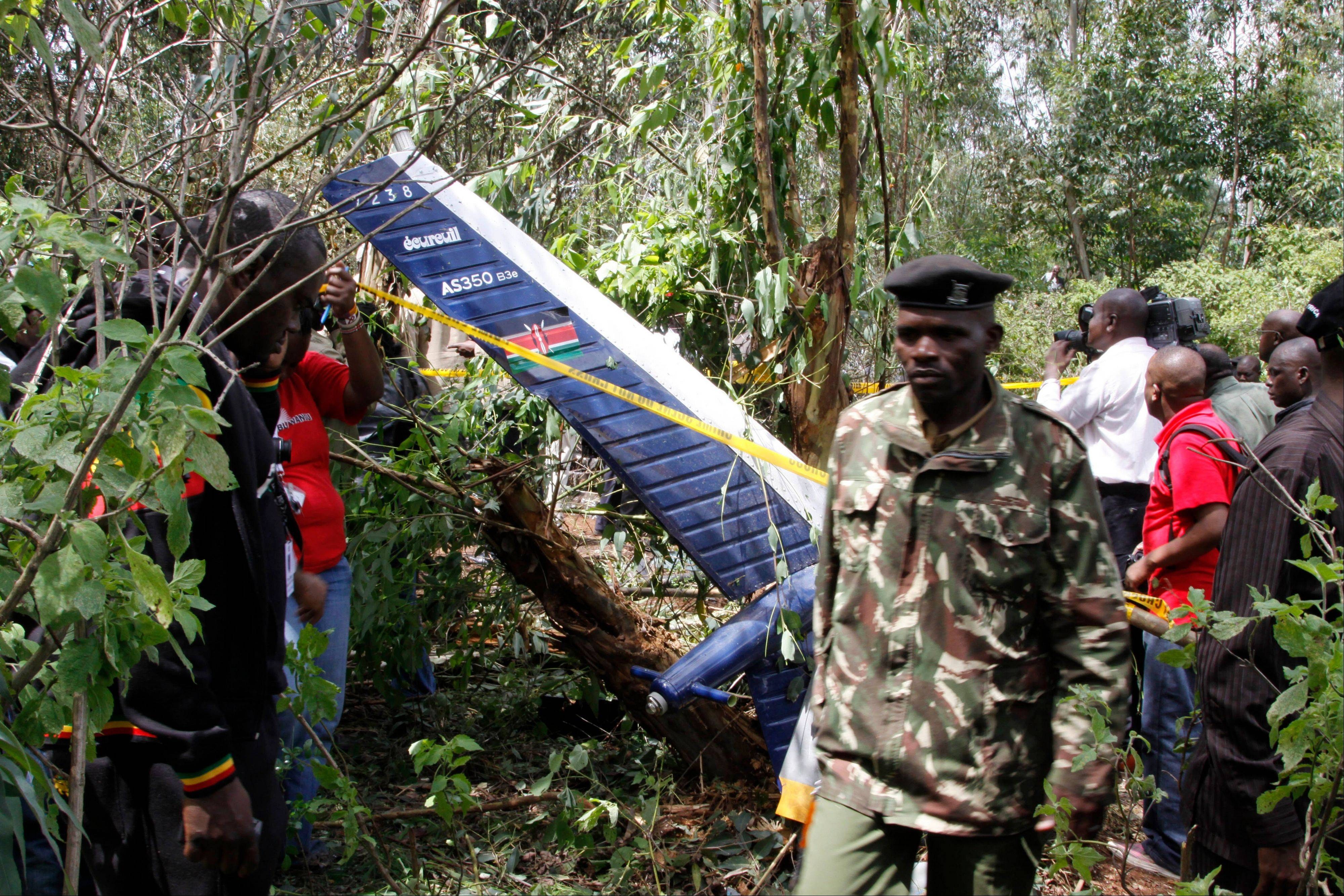 Kenyan officials inspect the area of the helicopter wreckage after it crashed Sunday in Ngong forest, on the outskirts of Nairobi, Kenya. Kenyan police say cabinet minister George Saitoti, who once served as Kenya's vice president, was one of seven people killed in a helicopter crash on the outskirts of Nairobi.