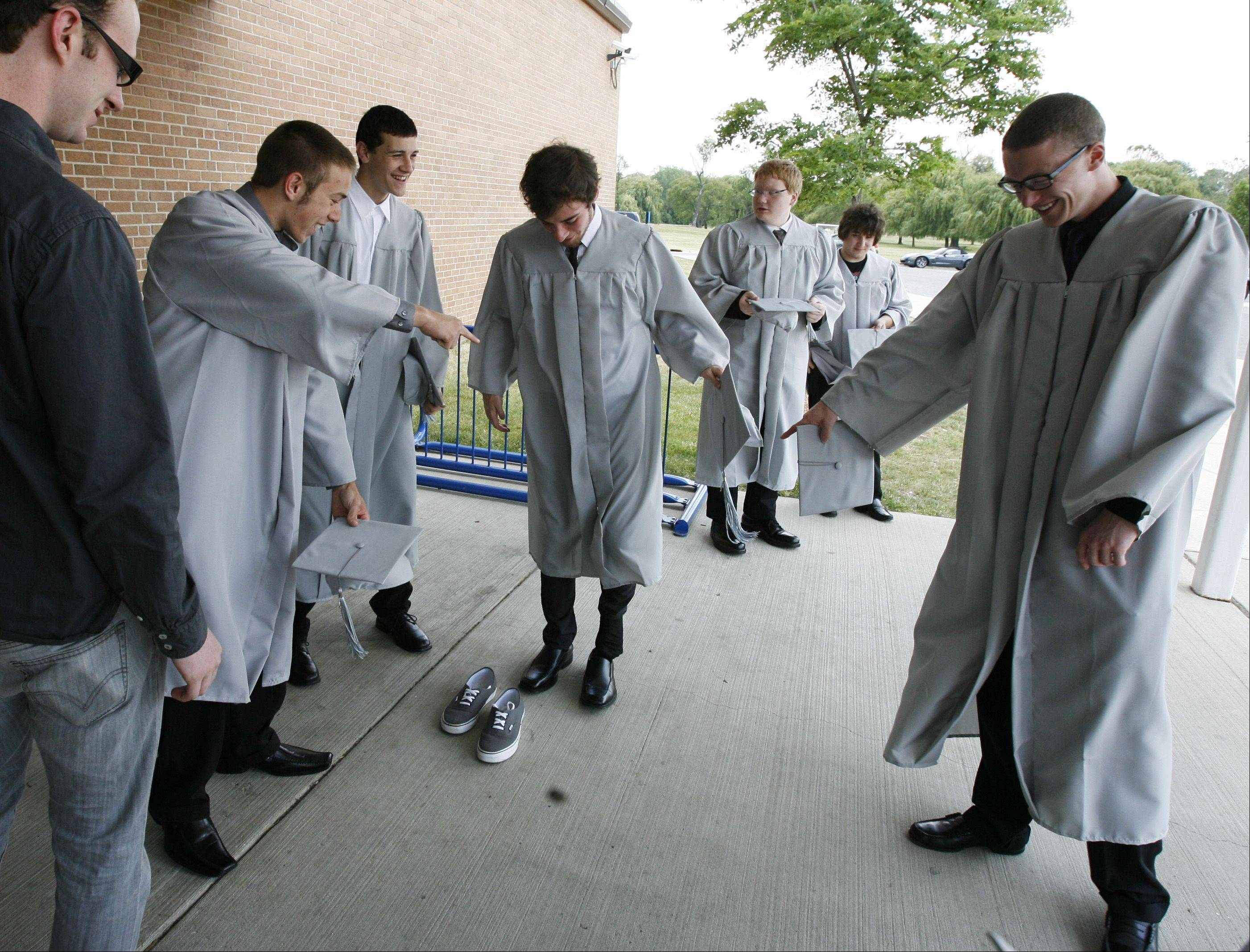 Matt Sutton, center, gets some fashion consulting from his friends to wear dress shoes before the Willowbrook High School graduation.