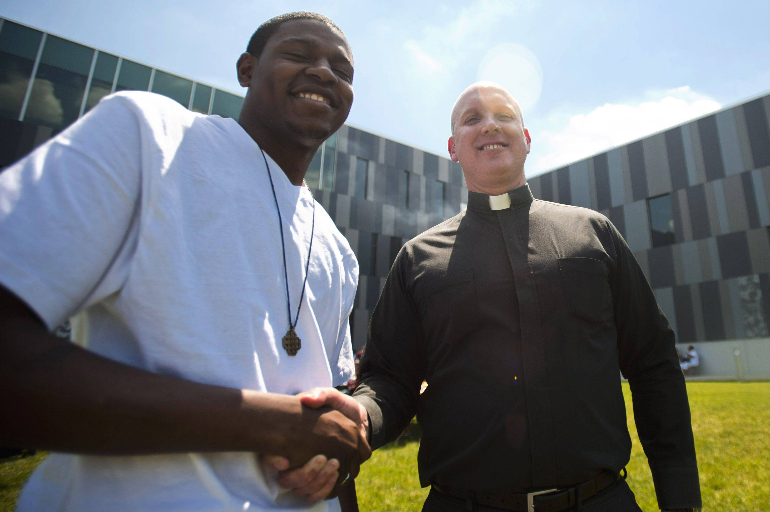Father Christopher Devron and graduate Stanley Coleman shake hands at the Christ the King Jesuit College Preparatory School, where all 53 members of the school's first graduating class have been accepted into college.