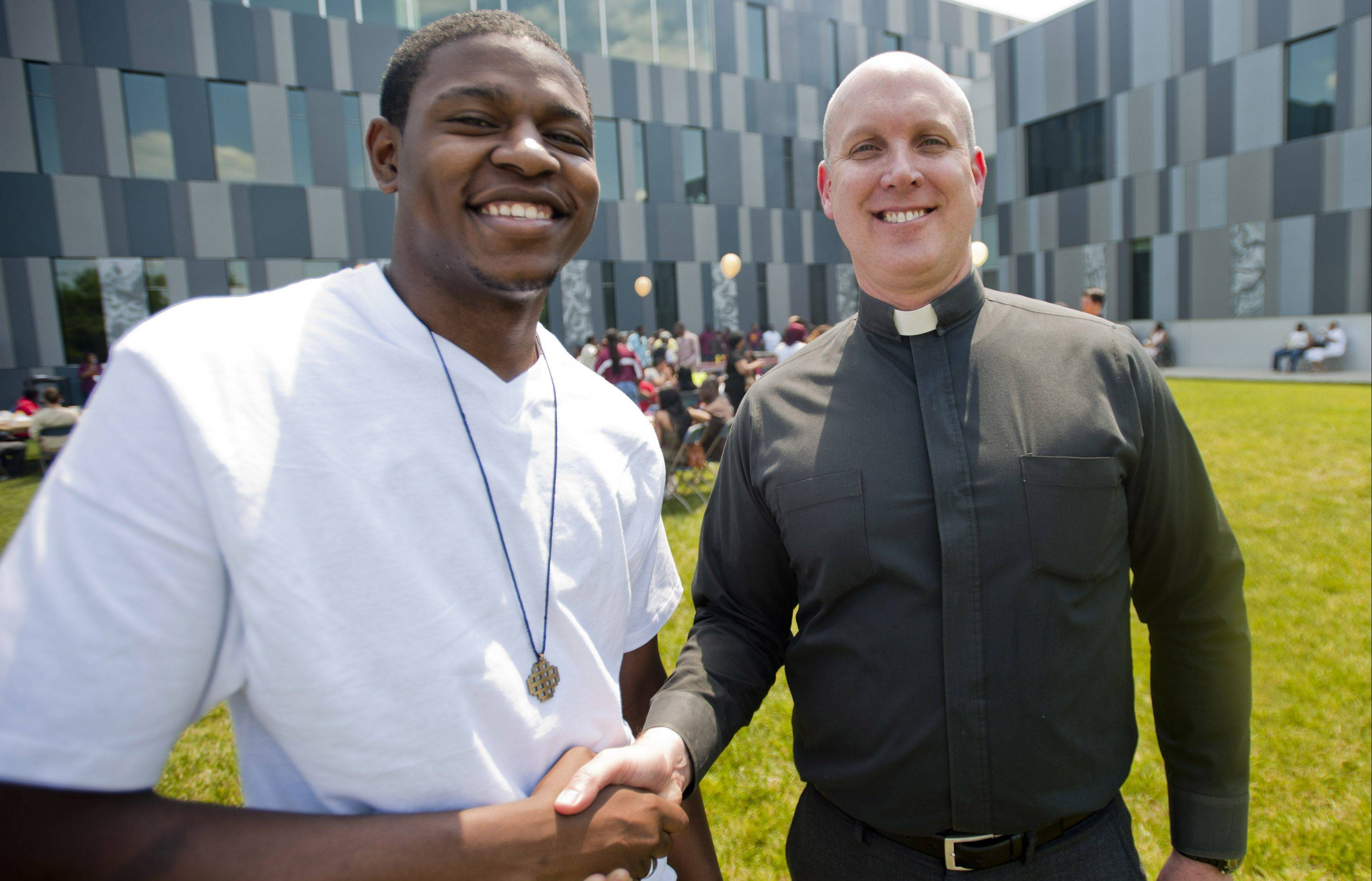 The Rev. Christopher Devron and graduate Stanley Coleman shake hands at the Chicago Jesuit Academy picnic, celebrating the 53 graduates of the school's first class Saturday.