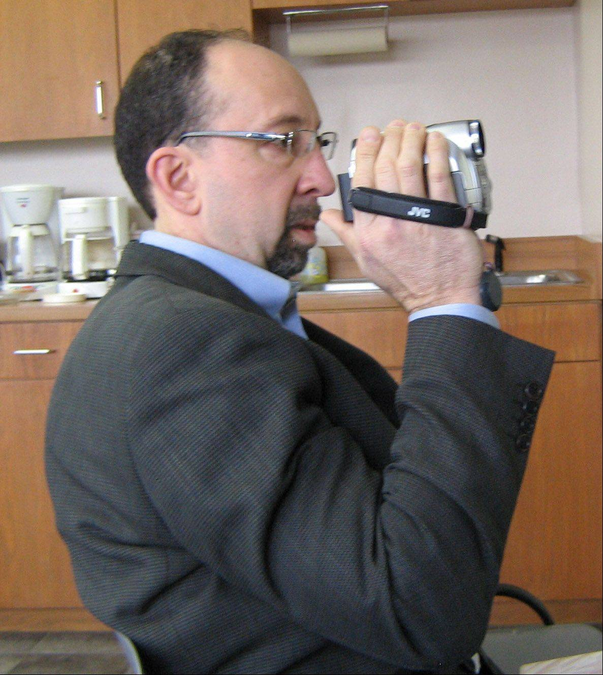 Ron Friedman, a Warren-Newport Public Library trustee, tapes a Lake County Housing Authority meeting in 2011.