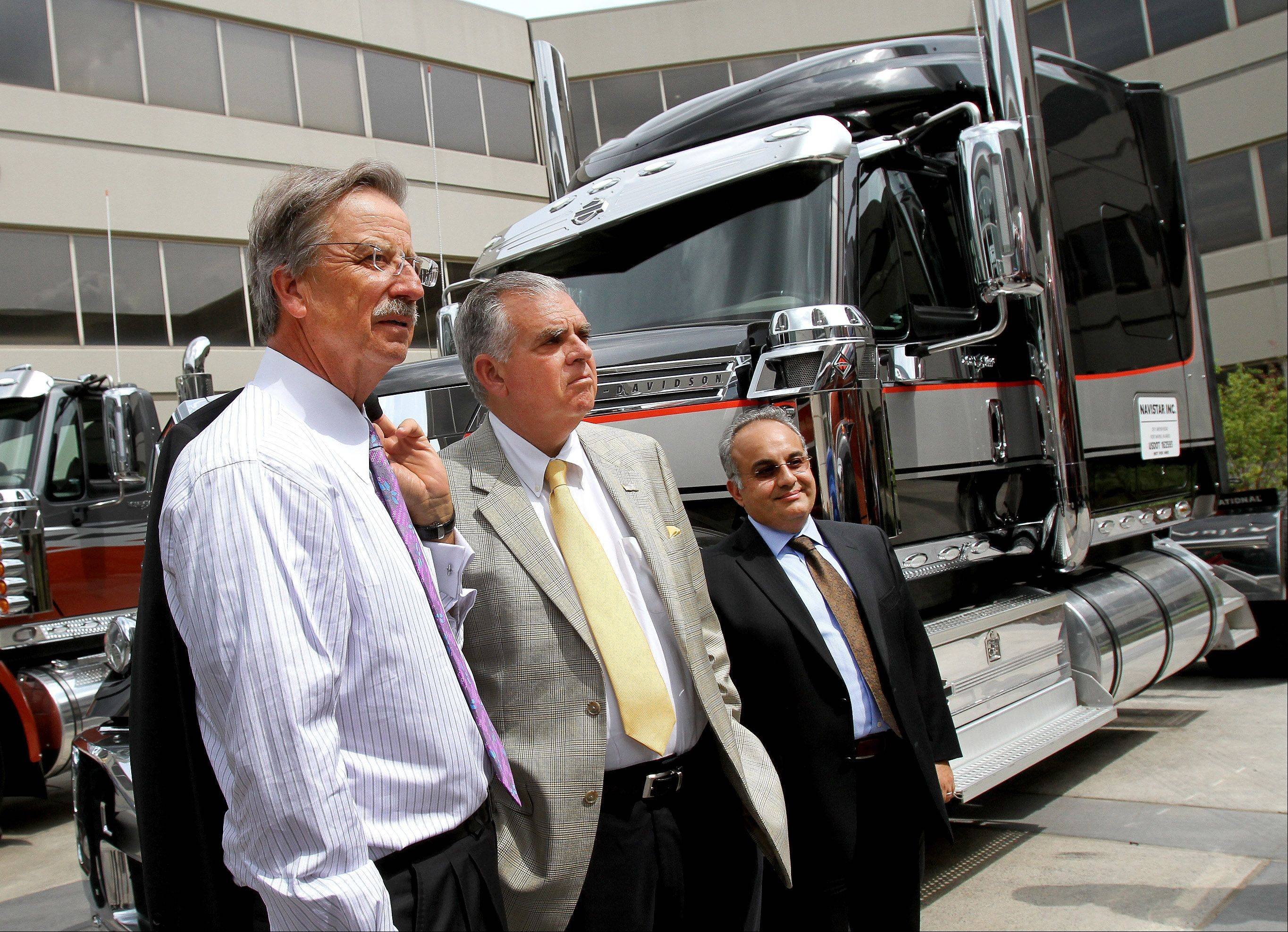 Dan Ustian, left, chairman, president and CEO and Ramin Younessi, right, group vice president of product development, show U.S. Transportation Secretary Ray LaHood, center, the latest inventory of trucks during his visit to Navistar in Lisle on Monday.