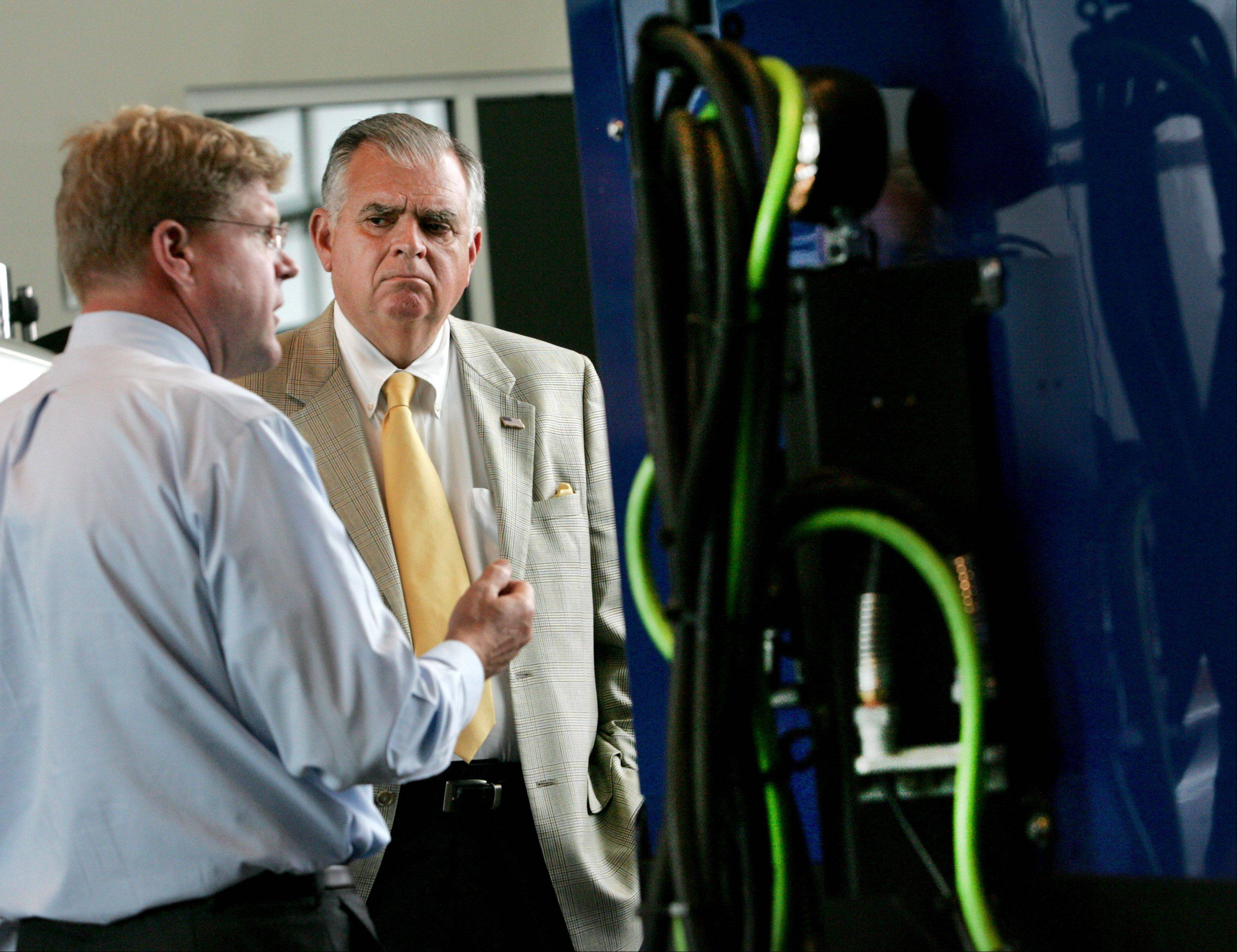 U.S. Transportation Secretary Ray LaHood listens to Dennis Mooney, left, vice president of engineering, as he looks at the latest inventory of trucks during a visit to Navistar in Lisle on Monday.