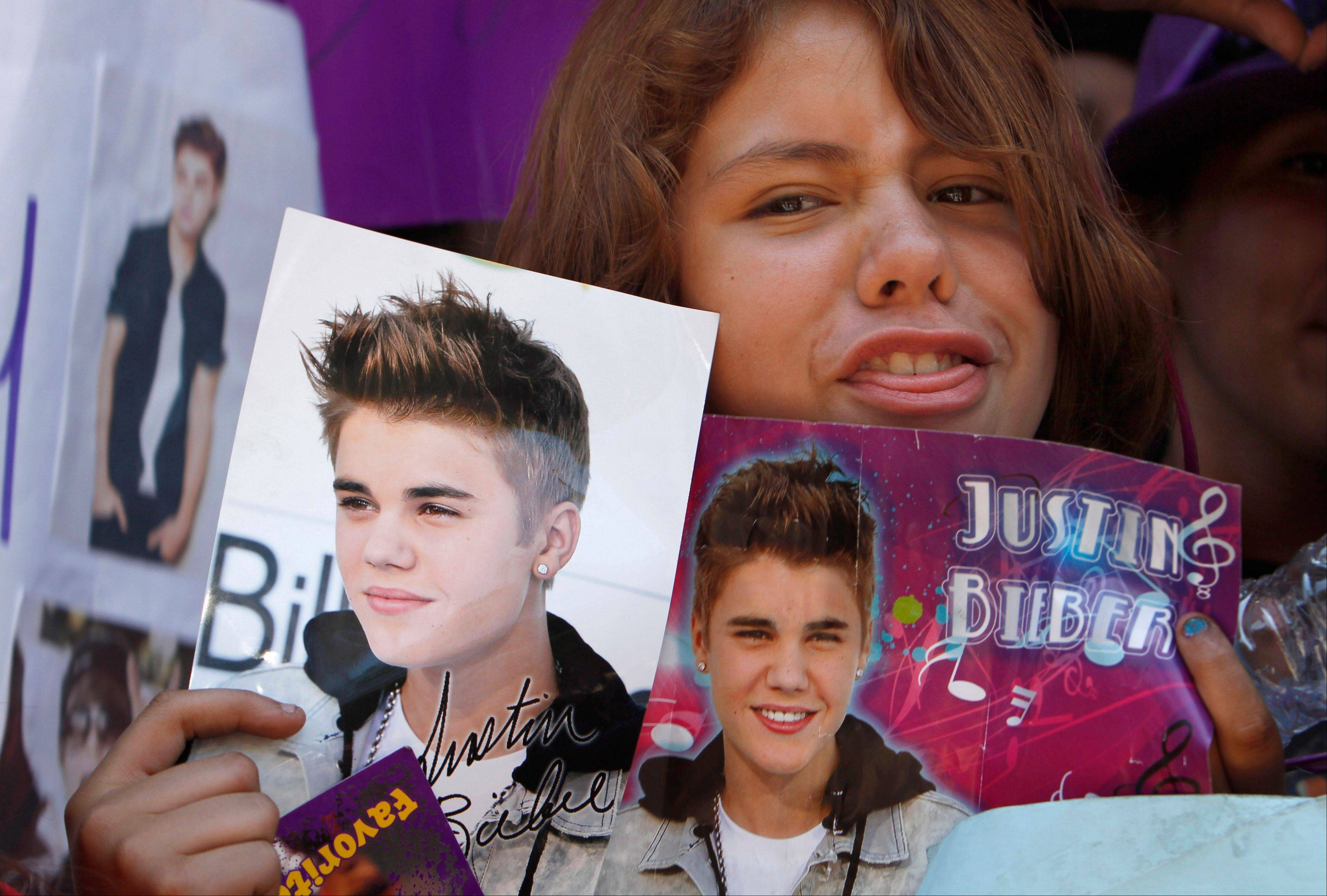A fan holds images of pop star Justin Bieber in Mexico City's main historic plaza.