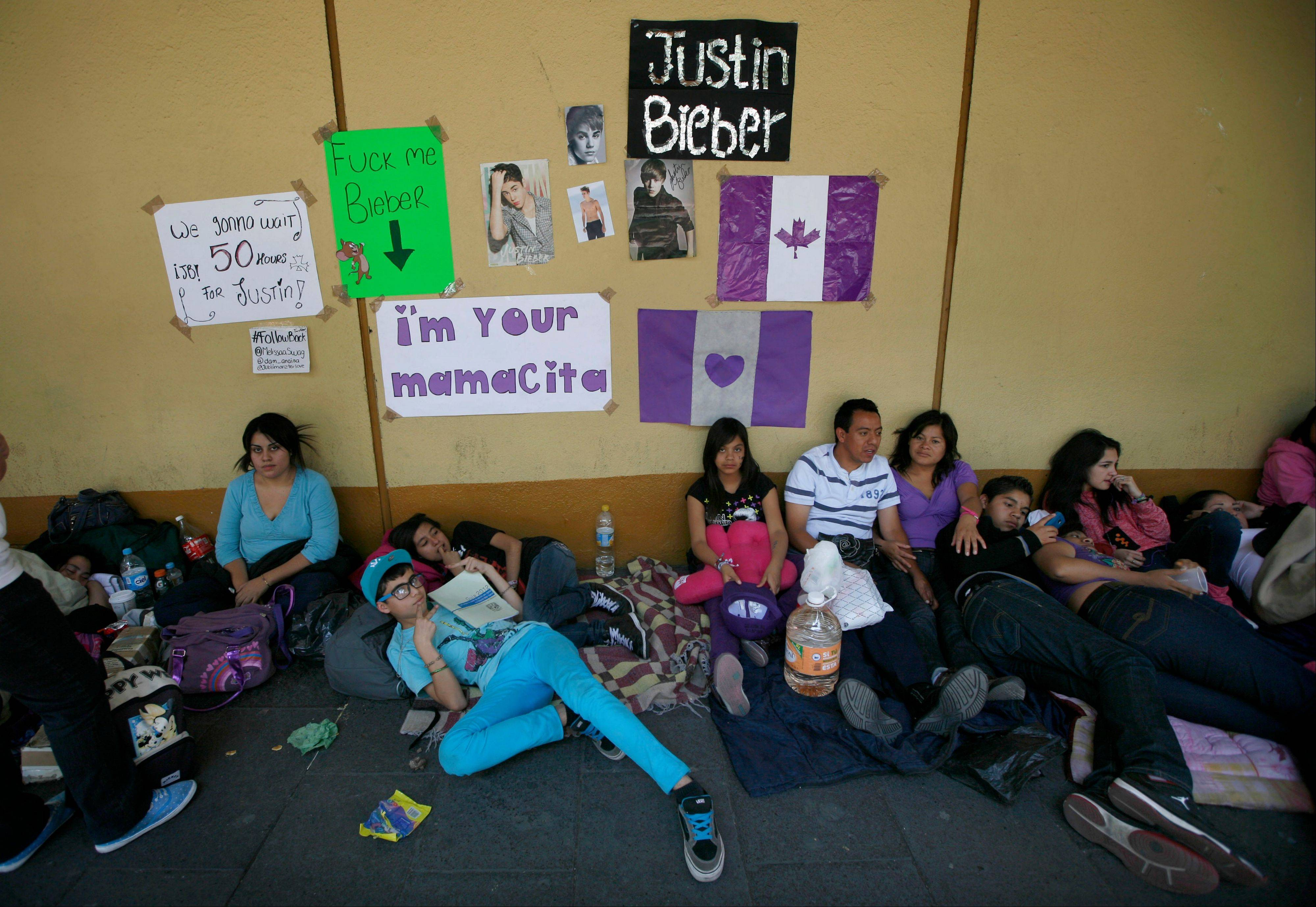 Fans with images of Canadian born pop singer Justin Bieber sit near Mexico City's main historic plaza Sunday. Adolescents in purple and white and braved two nights on roach-infested sidewalks for a chance to be closest to the stage when teenage superstar Justin Bieber puts on a free concert Monday night.