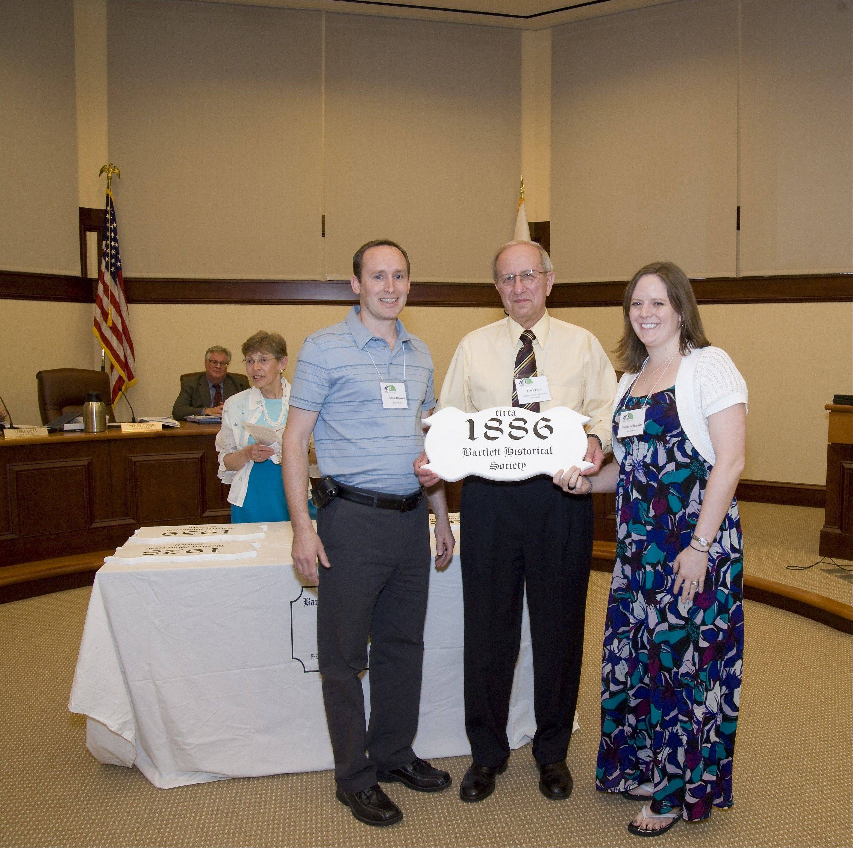 Bartlett Historical Society President Gary Plice presents a plaque to Adam and Stephanie Hopkins, owners of a barn at 225 N. Tatge Avenue.